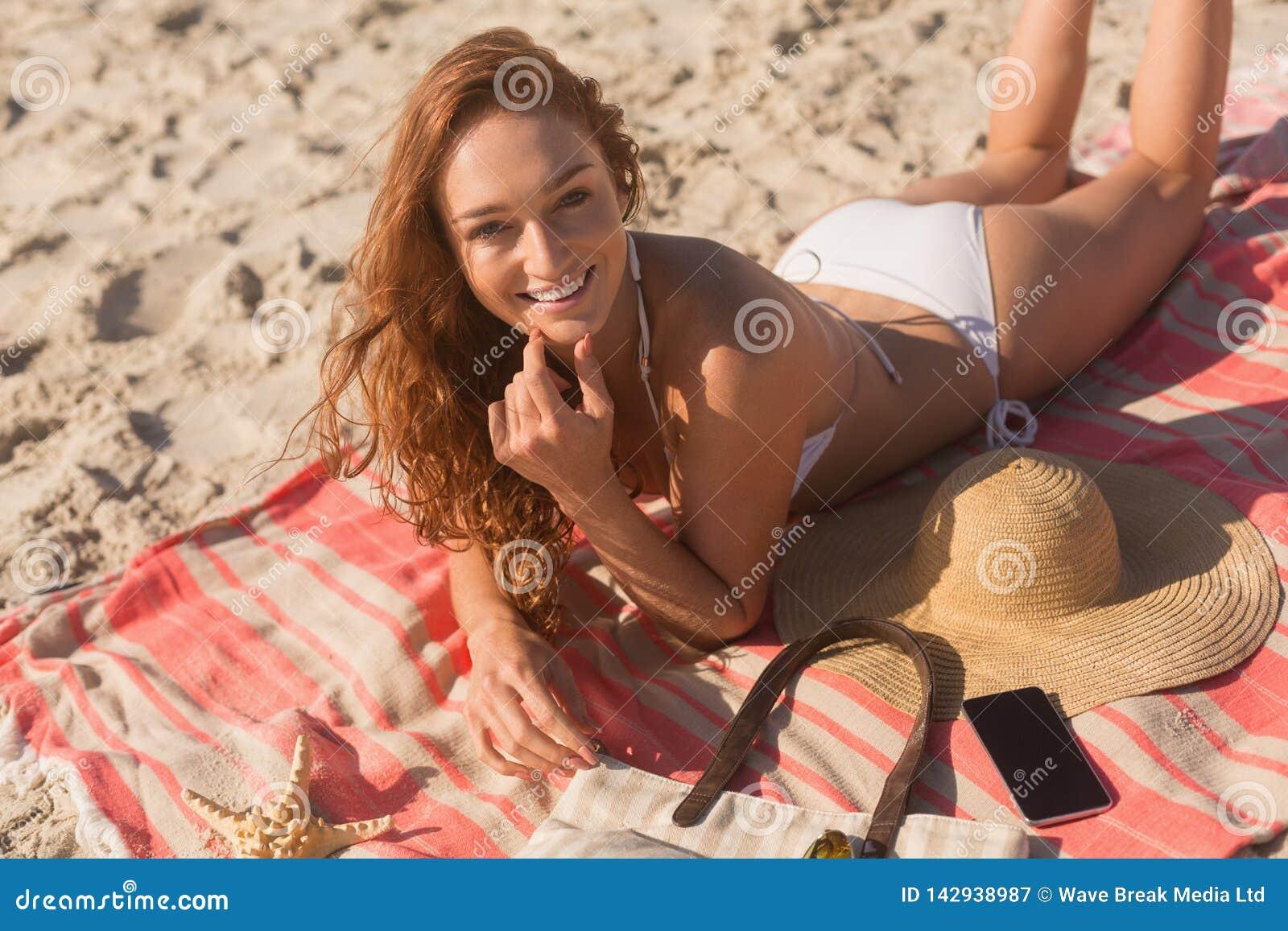 Junge kaukasische Frau im Bikini, der auf Sand liegt und Kamera auf dem Strand betrachtet