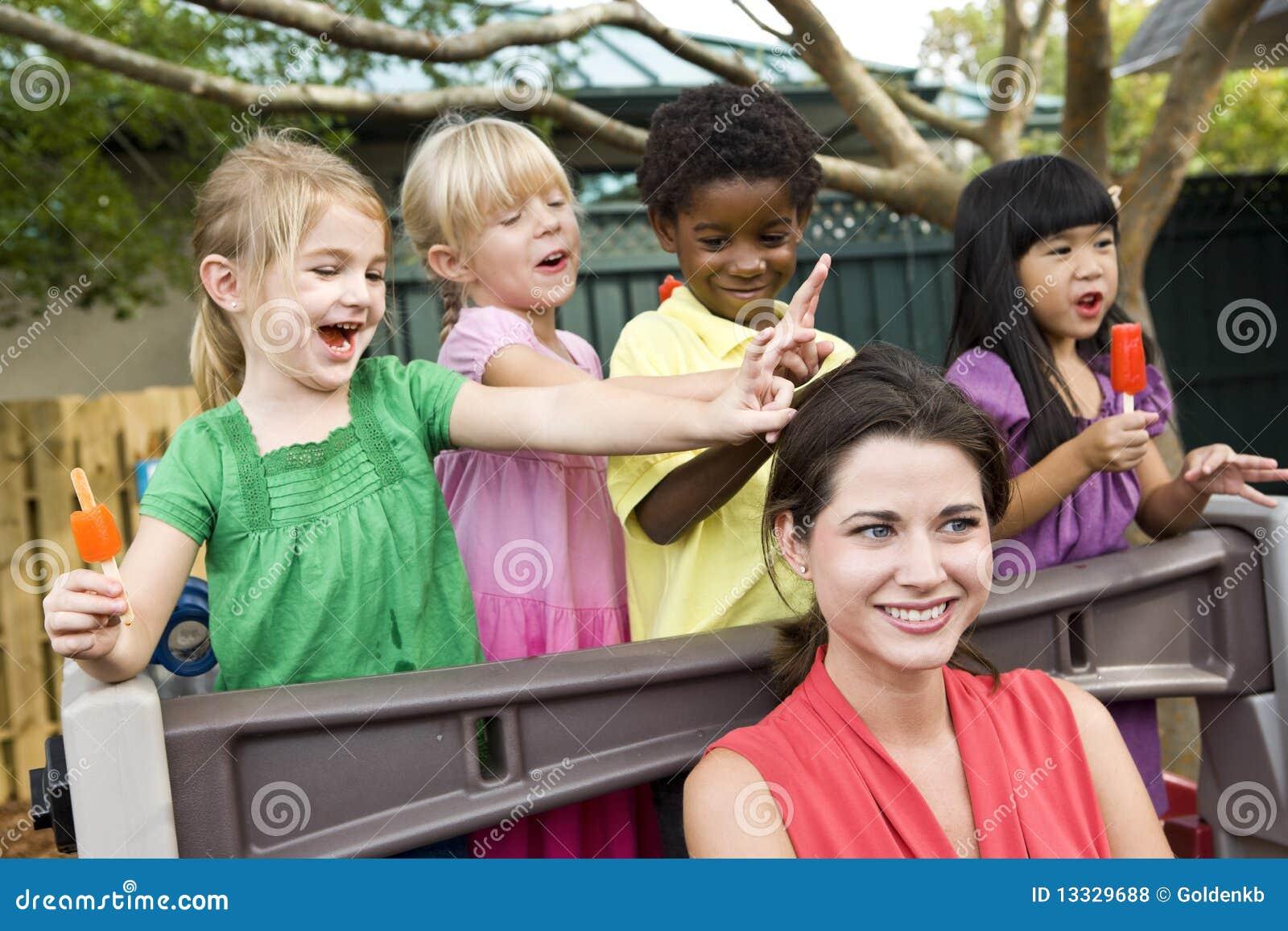 Junge Kinder, die in der Kindertagesstätte mit Lehrer spielen