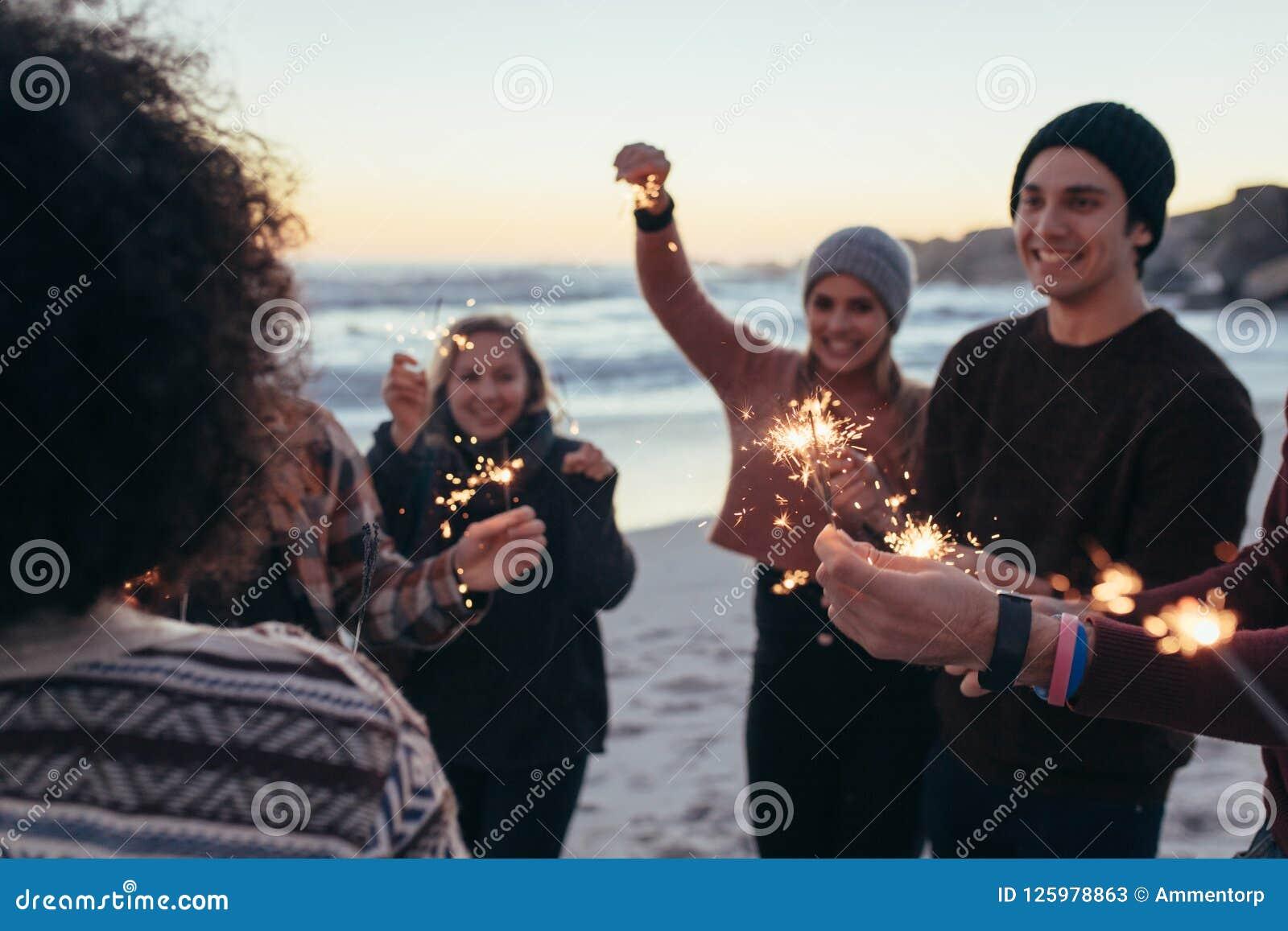 Junge Leute, die Spaß mit Wunderkerzen am Strand haben