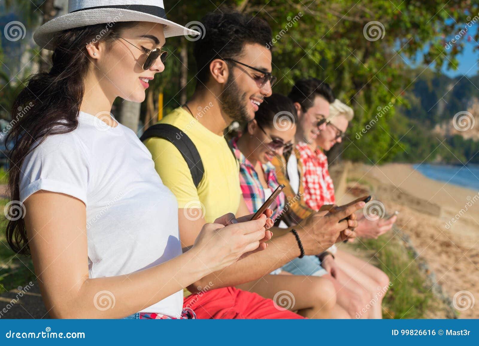 Junge Leute-Gruppe unter Verwendung der Zelle Smart ruft die tropischen Park-Palme-Freunde an, die on-line-Feiertags-Seesommer-Fe