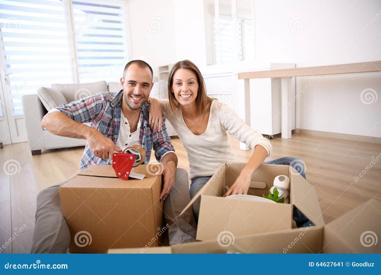 Junge Leute mit den cardboxes, die einziehen