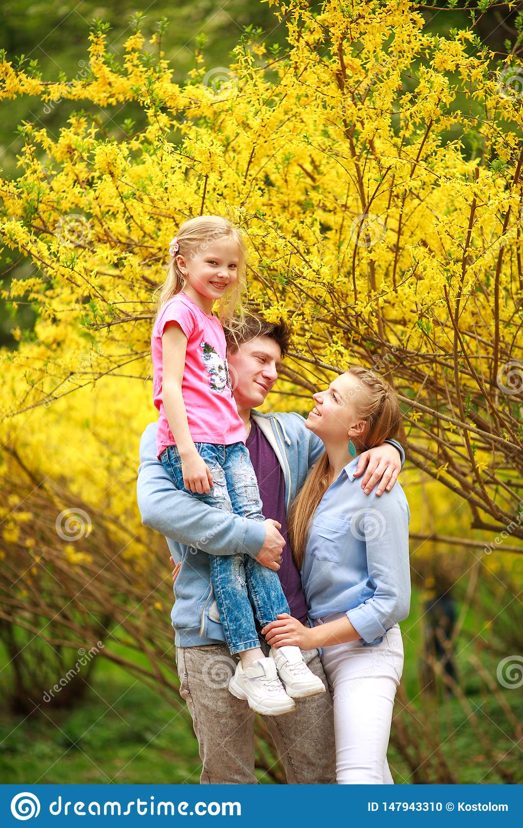 Junge liebevolle Paare von Eltern mit Kindertochter im Park auf Hintergrund des gelben bl?henden Baums