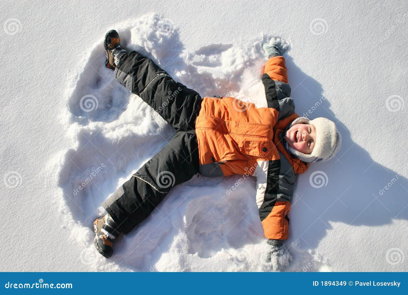 Junge liegt auf Schnee