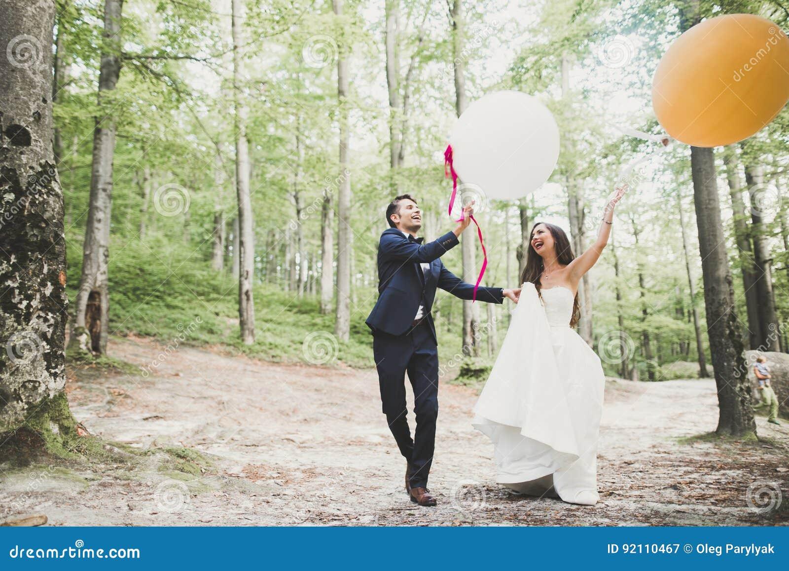 Junge lustige glückliche Hochzeitspaare draußen mit Ballons