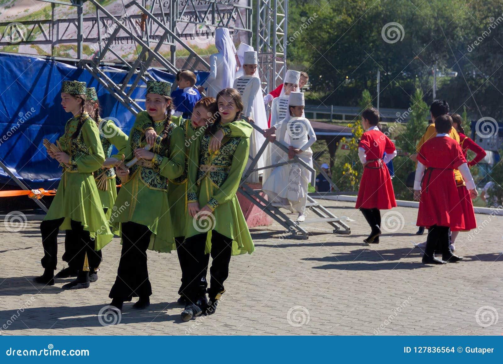 Junge Mädchen und Jungenkünstler in der traditionellen Circassian Kleidung bereiten vor sich, am Festival von Adyghe-Käse in den
