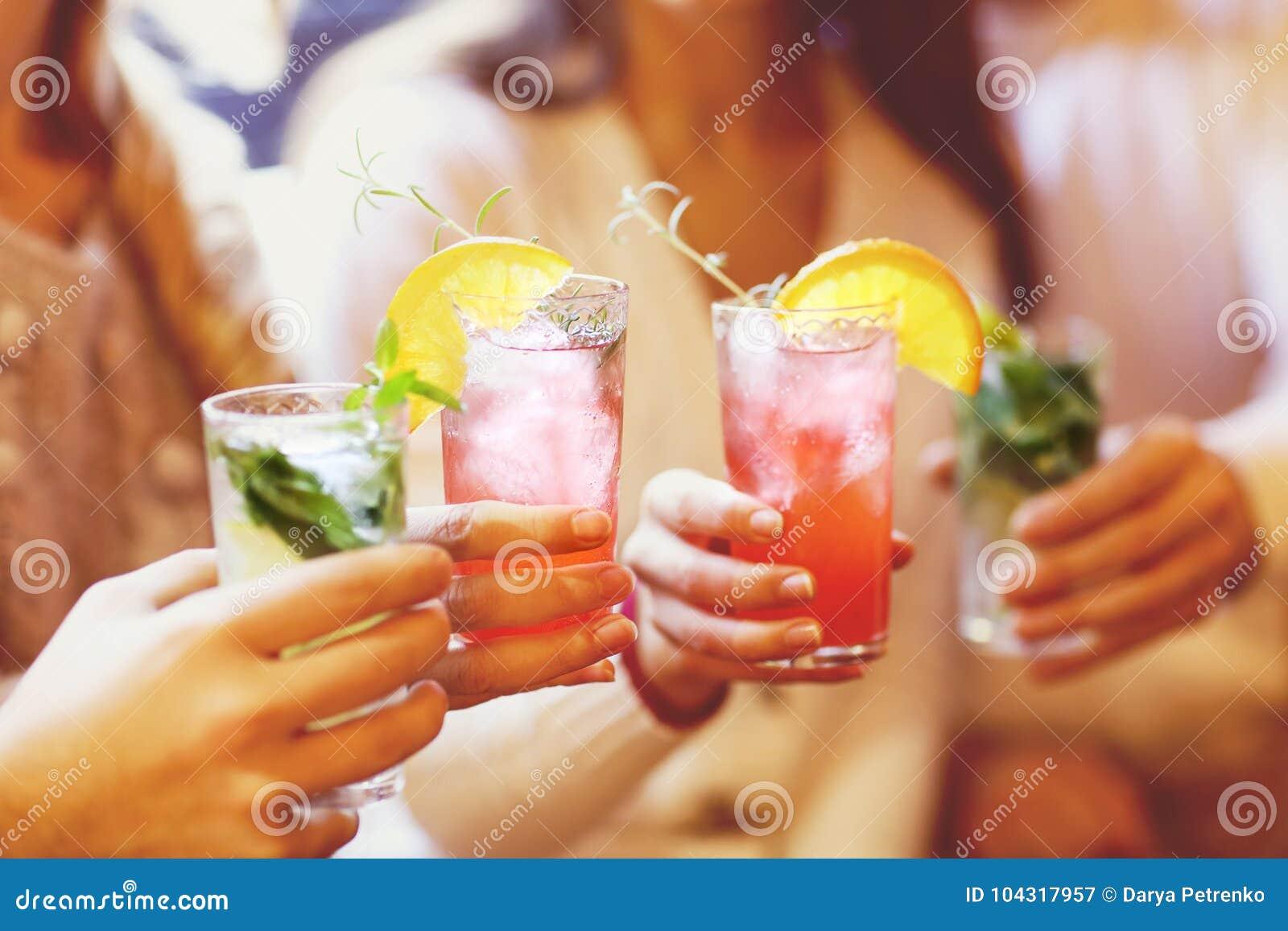 Junge Männer und Frauen, die Cocktail an der Partei trinken