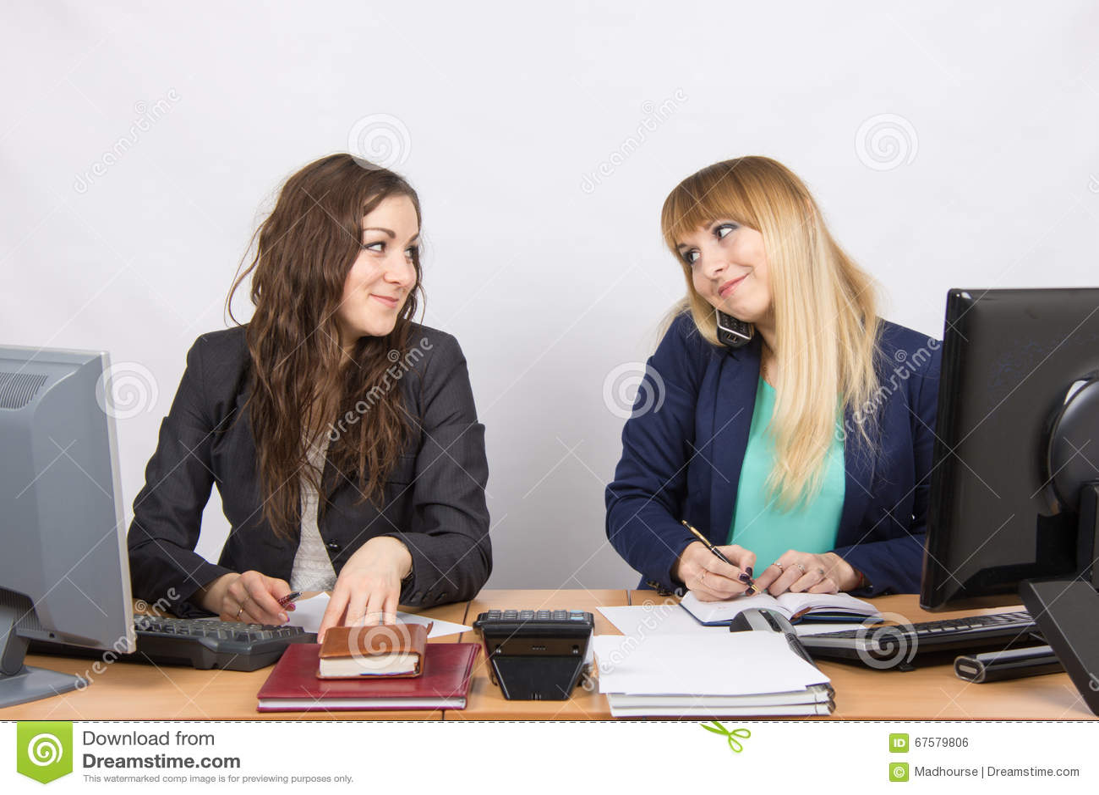 Zwei junge hübsche Geschäftsfrauen, die an einem Bürotisch sitzen ...