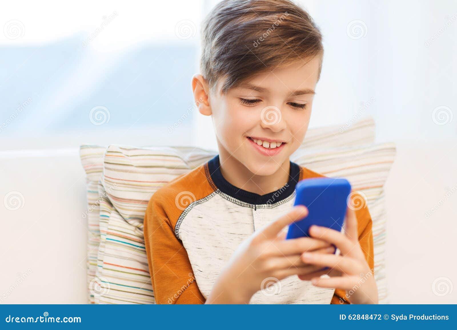 junge mit dem smartphone der zu hause simst oder spielt stockfoto bild von lebensstil. Black Bedroom Furniture Sets. Home Design Ideas
