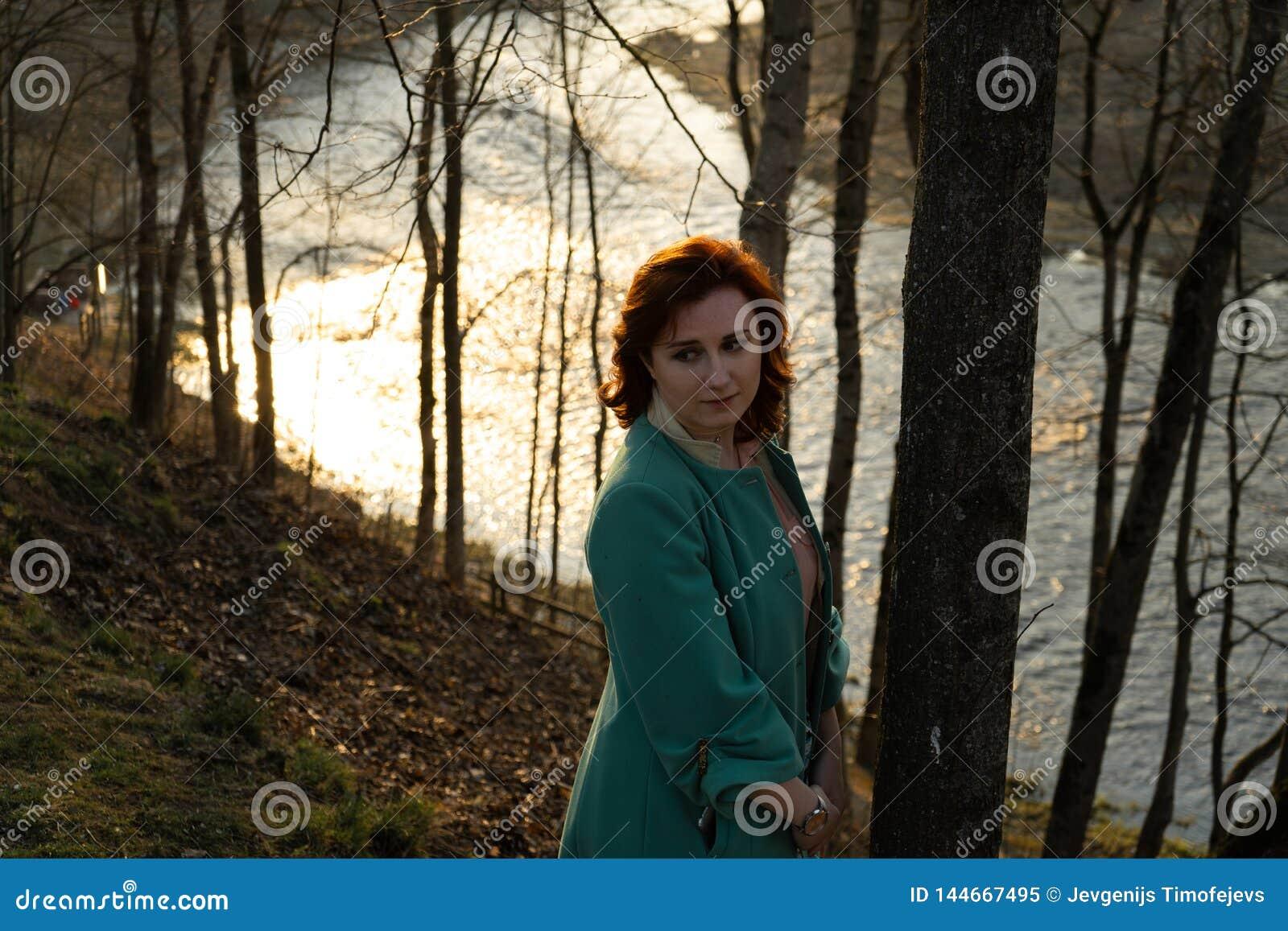 Junge Modefrau, die Sonnenuntergang nahe einem Fluss in Bauska, Lettland, 2019 sich entspannt und genießt