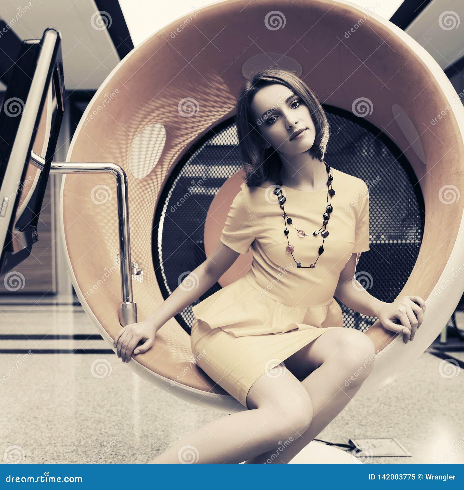 Junge ModeGeschäftsfrau, die auf Computerstuhl im Büro sitzt