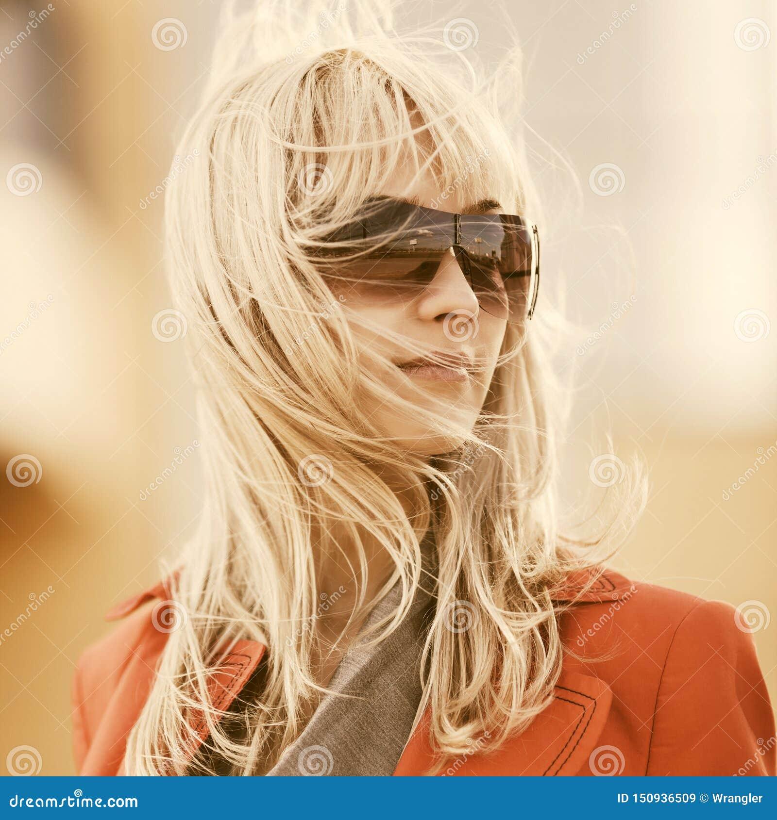 Junge ModeGesch?ftsfrau in der Sonnenbrille gehend auf Stadtstra?e