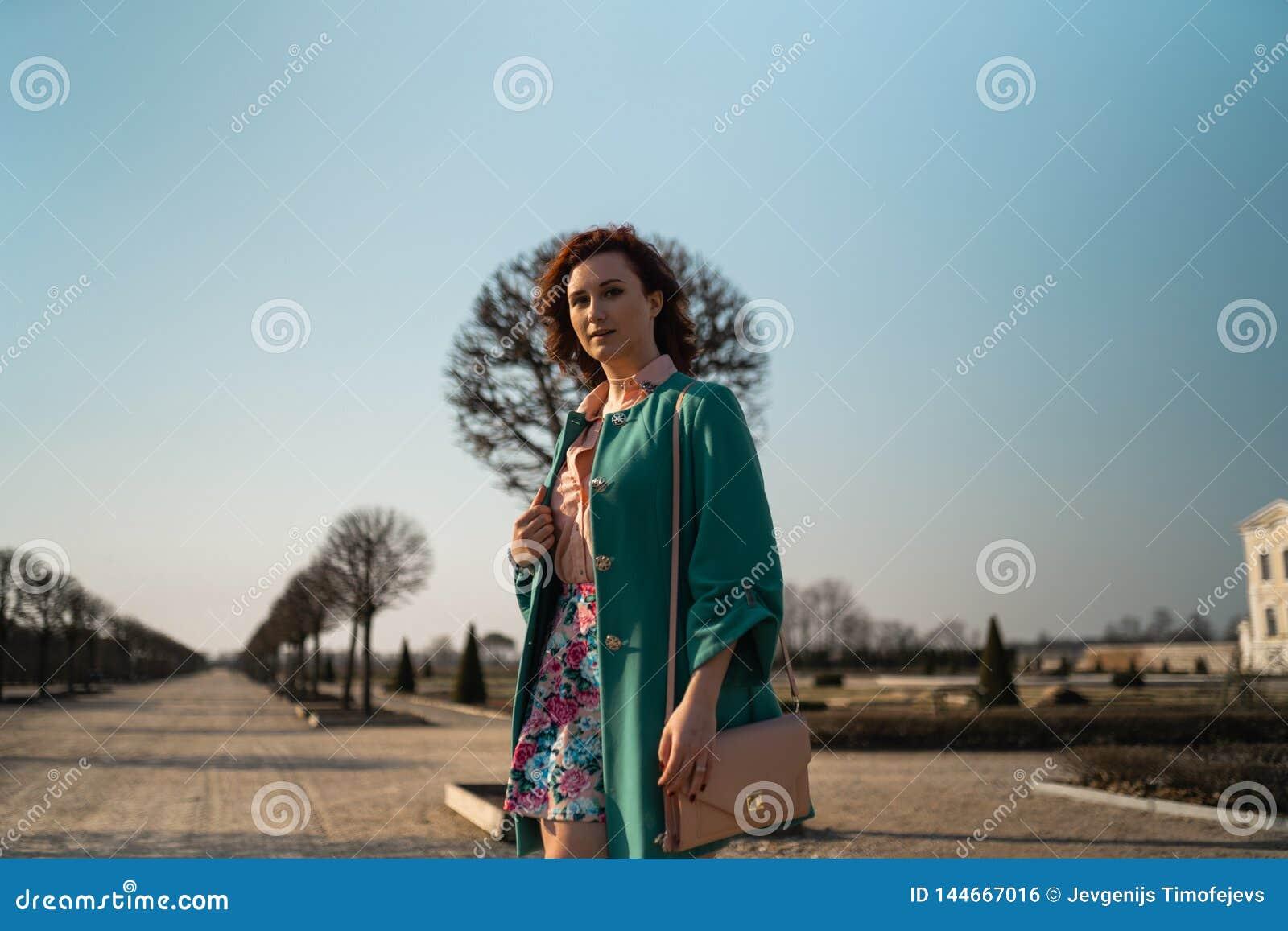 Junge Modeliebhaberfrau, die in einem Park trägt klare grüne Jacke und einen bunten Rock waling ist