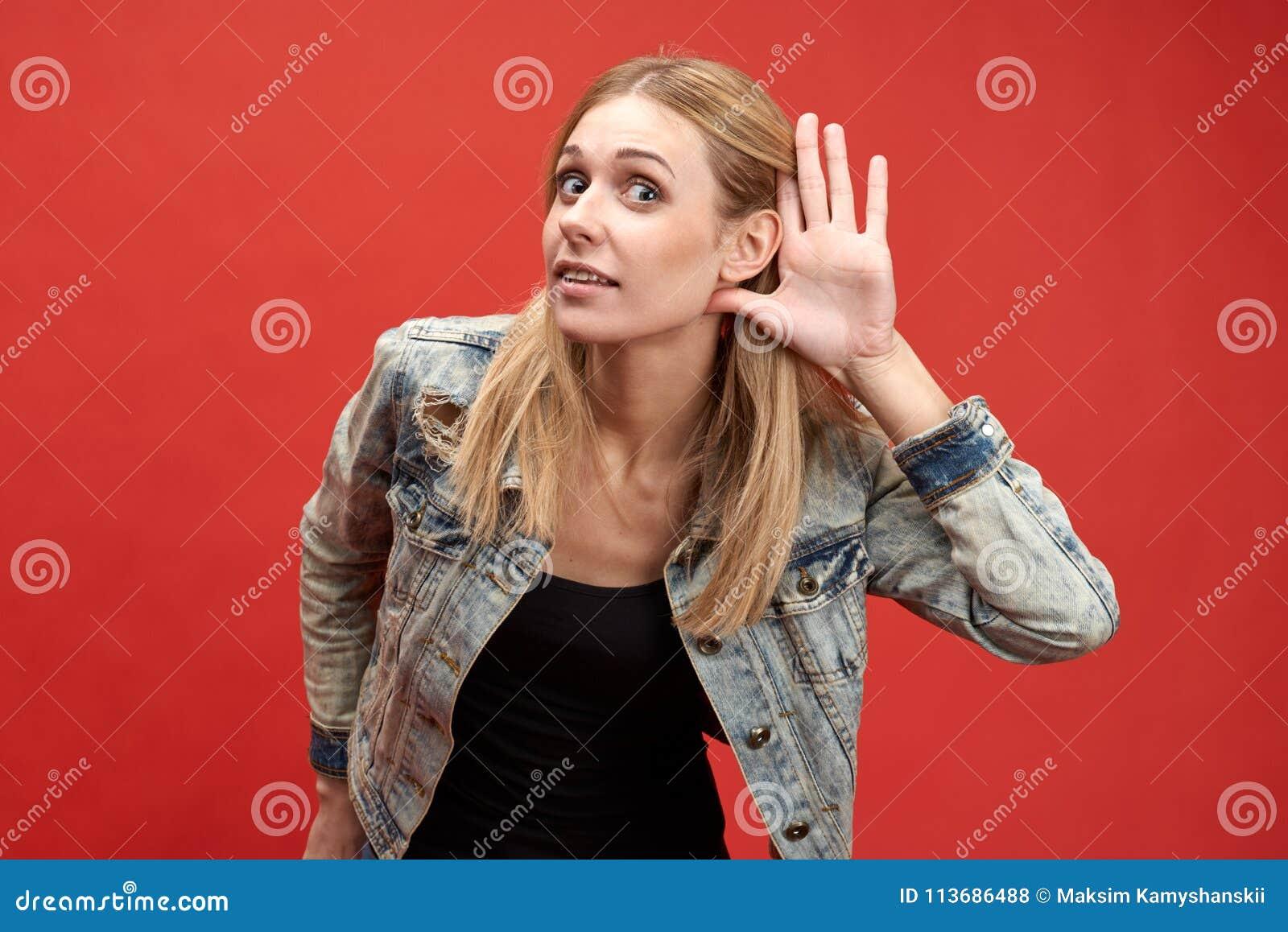 Junge moderne stilvolle Frau setzt malerisch ihre Hand zu ihrem Ohr in ein Zeichen aufmerksam von hören oder von Heimlich zuhören