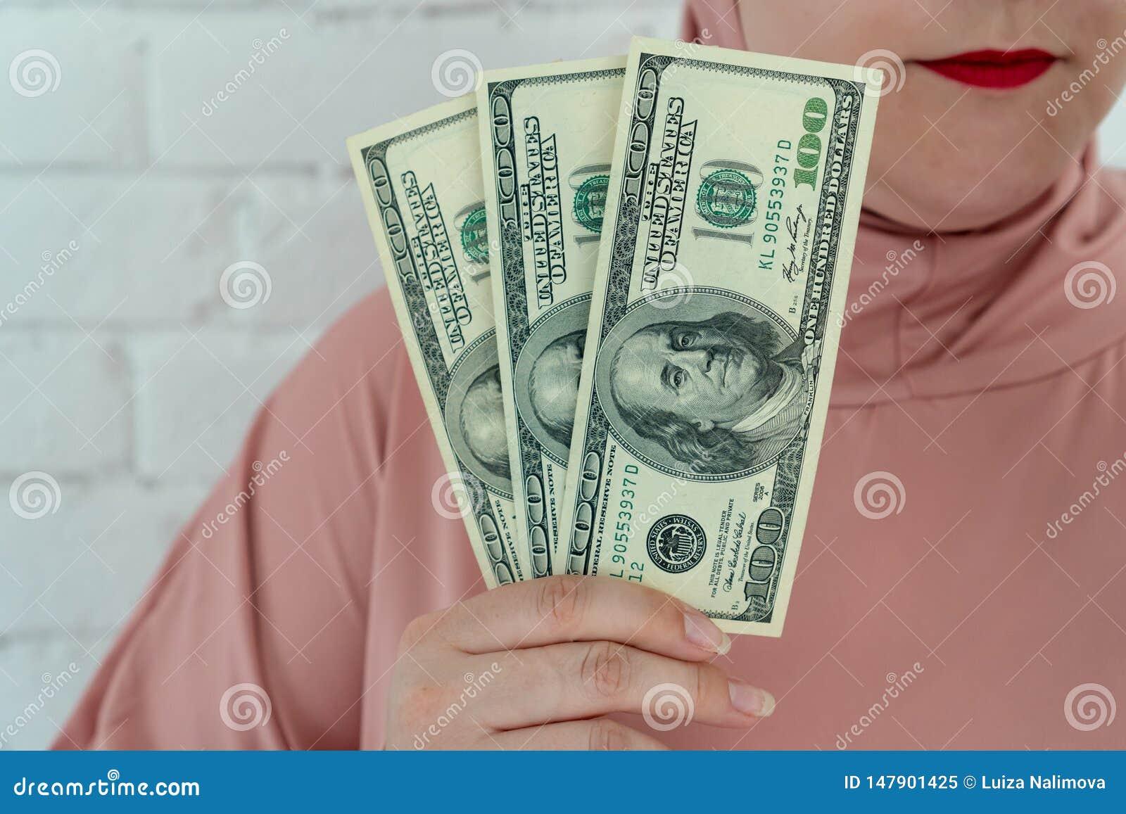 Junge moslemische Frau in rosa hijab Kleidung halten vom Bargeld in Dollarbanknoten a in ihren Händen