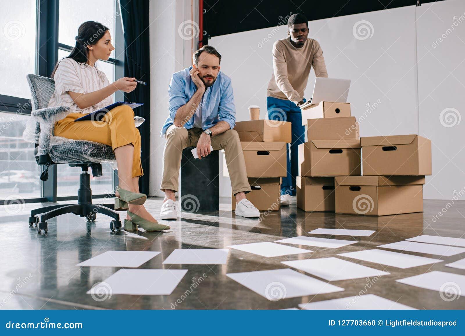 Junge multiethnische Geschäftsleute, die Papiere auf Boden in neuem betrachten