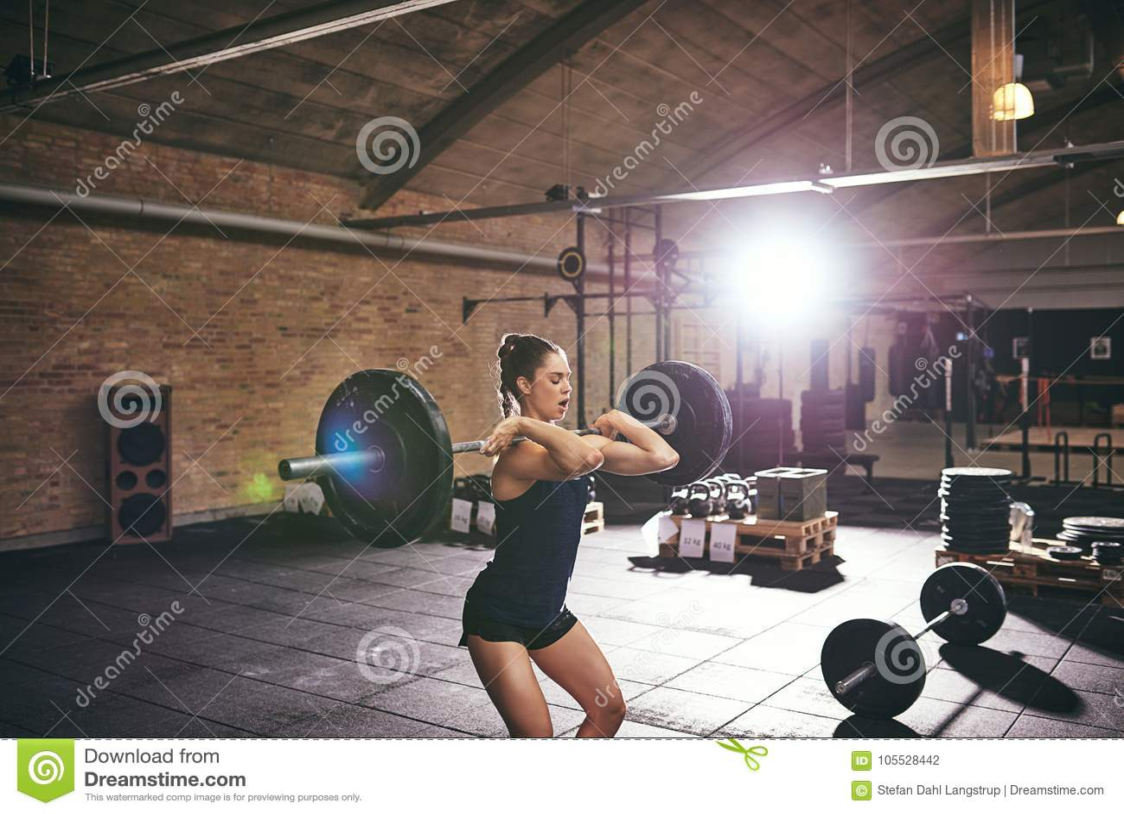 Junge muskulöse Frau anhebende Barbells in der Turnhalle