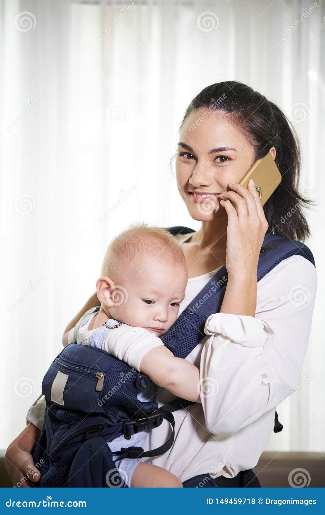 Junge Mutter, die am Telefon spricht