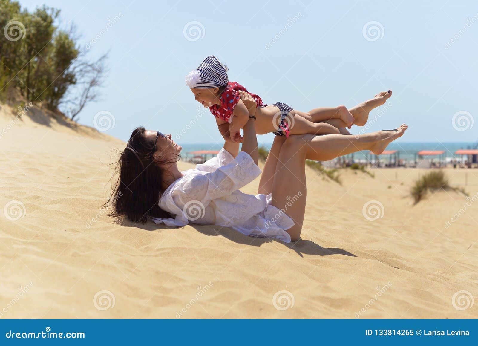 Junge Mutter mit weniger Tochter, die Spaß auf dem sandigen Strand hat