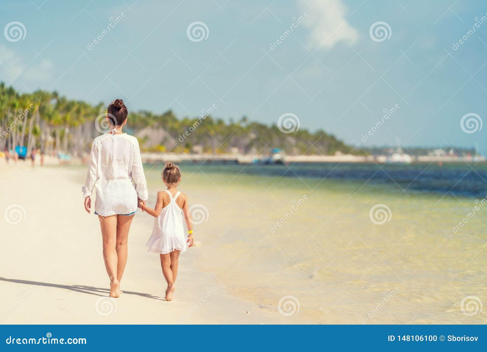 Junge Mutter und kleine Tochter, die den Strand in der Dominikanischen Republik genie?t