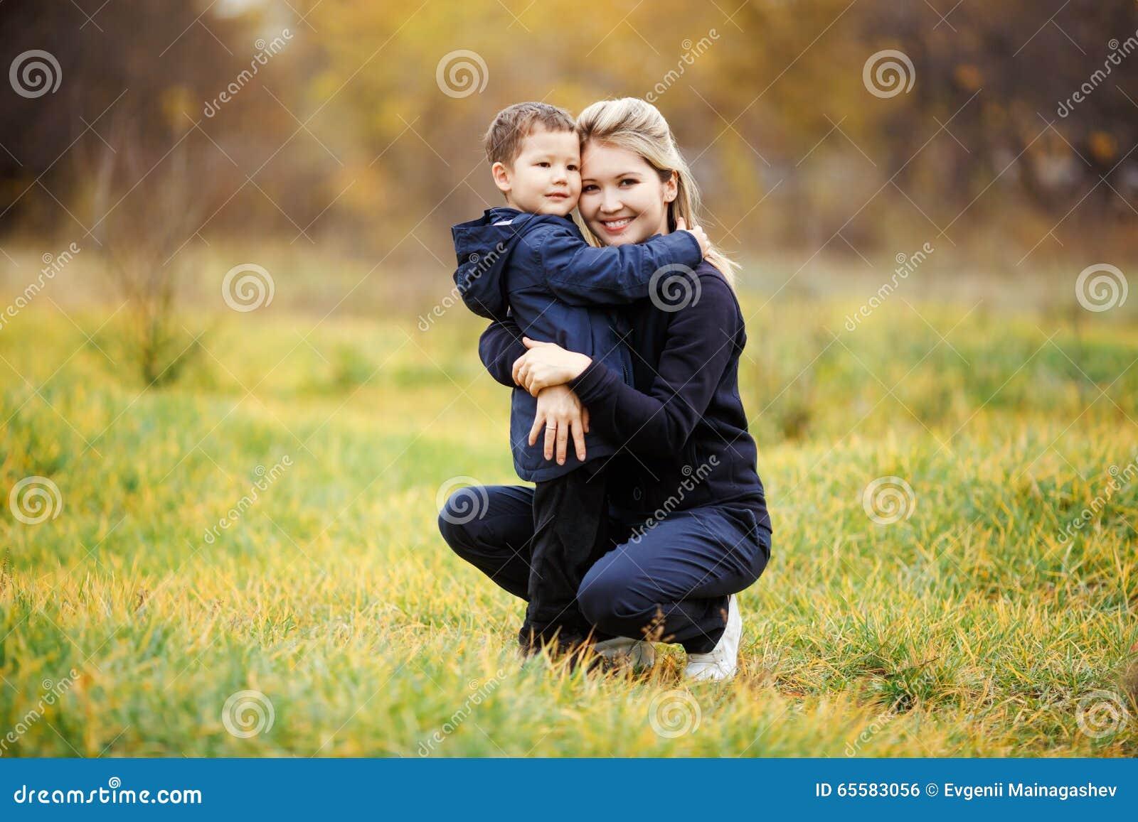 Junge Mutter und Sohn im Herbst Forest Park, gelbes Laub beiläufige Abnutzung Kindertragender Matrose Unvollständige Familie