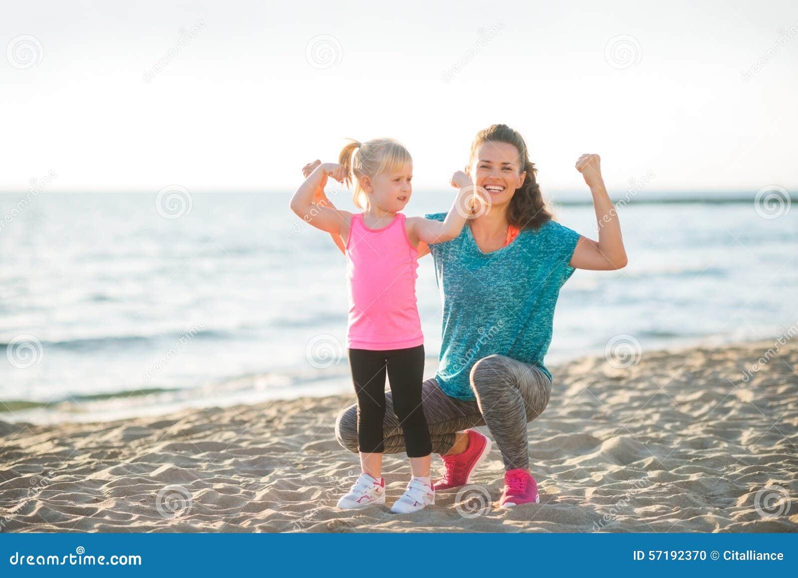 Junge Mutter und Tochter in der Eignung übersetzen auf dem Strand, der Arme biegt