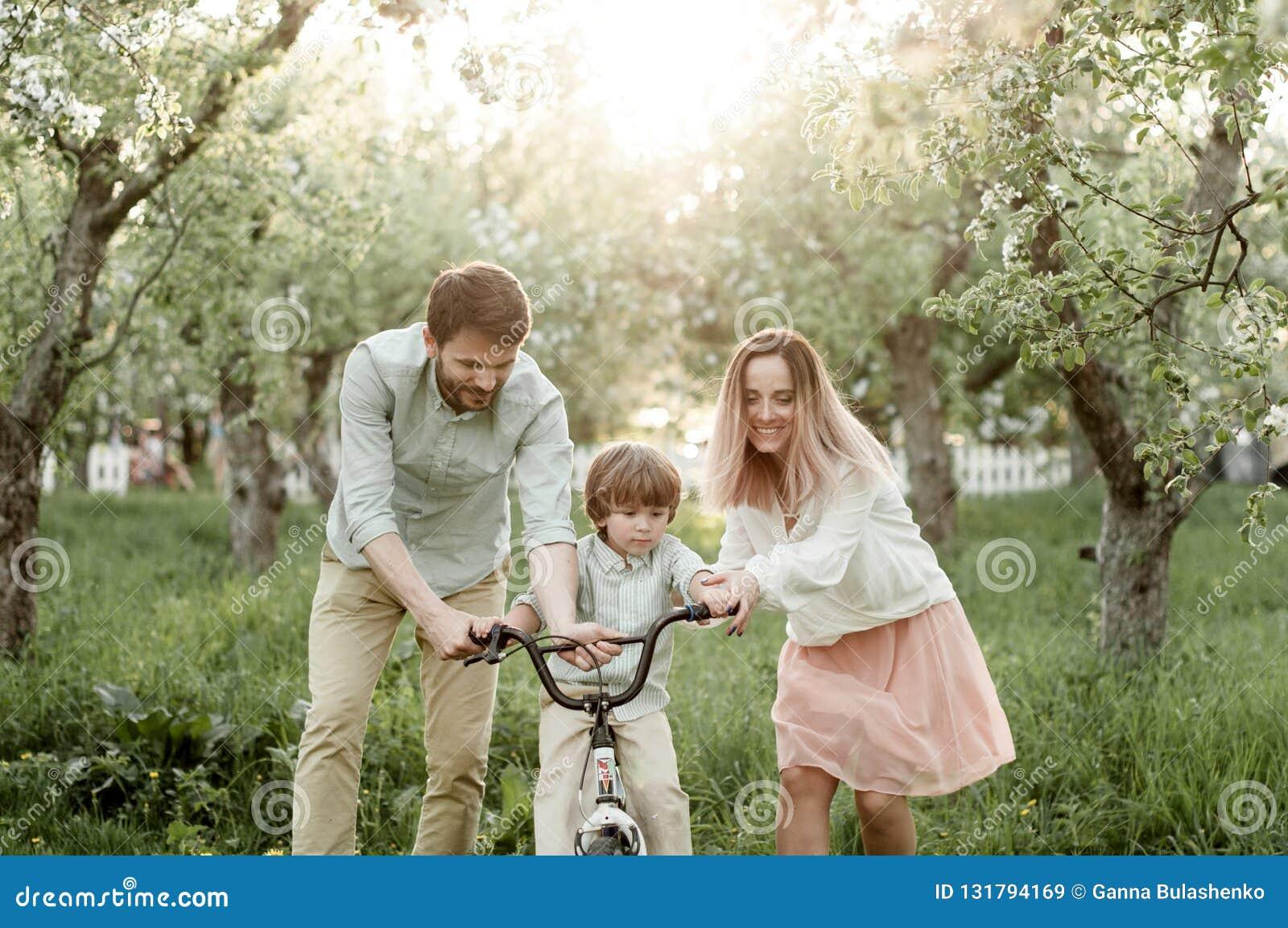 Junge Mutter und Vati unterrichten ihren Sohn, ein Fahrrad zu reiten