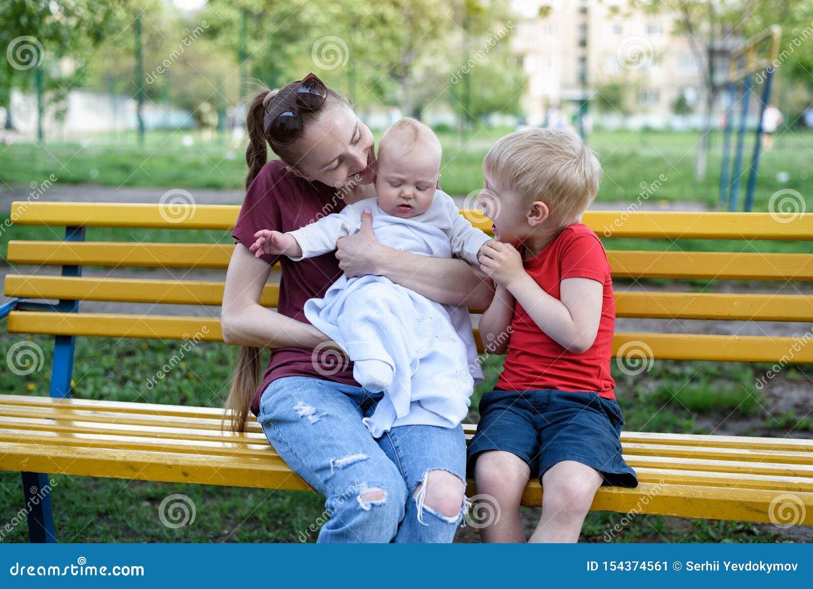 Junge Mutter und zwei Kinder auf einer Bank im Park Baby und blondes Spielen des älteren Bruders Warmer Tag des Fr?hlinges
