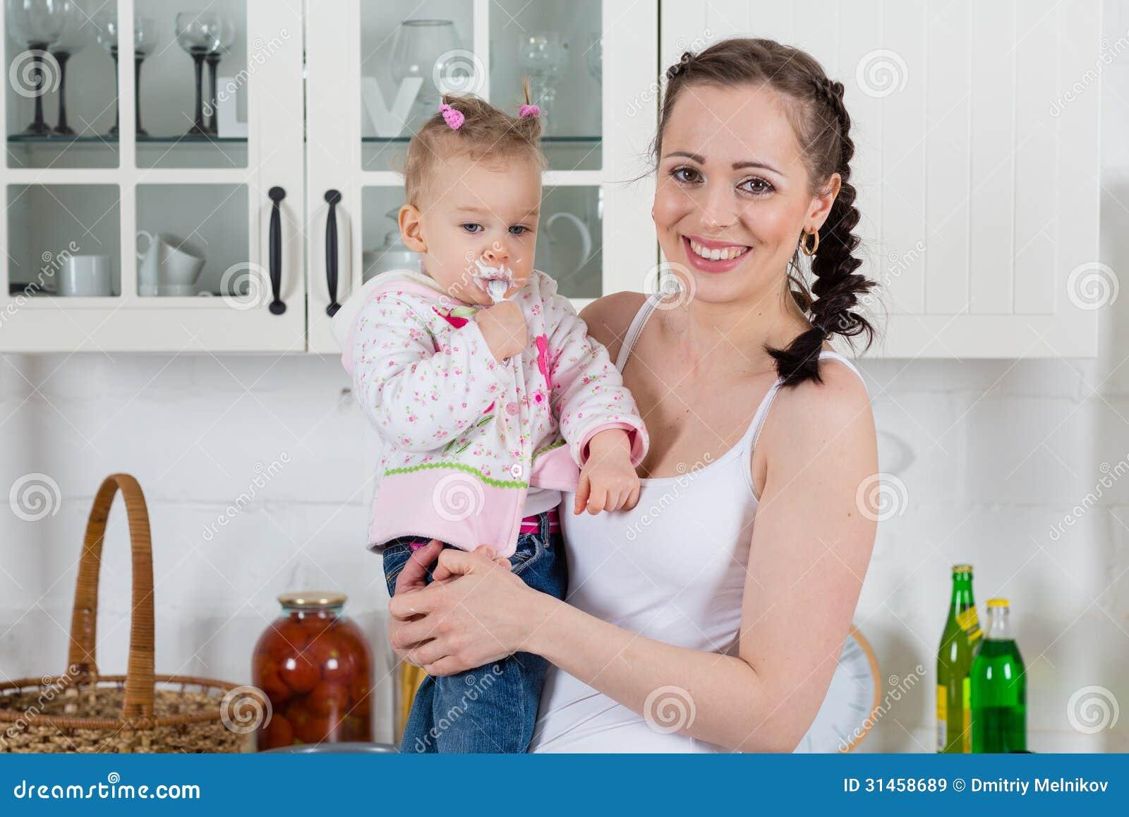 Junge Mutter Zieht Kind In Der Küche Ein. Lizenzfreie