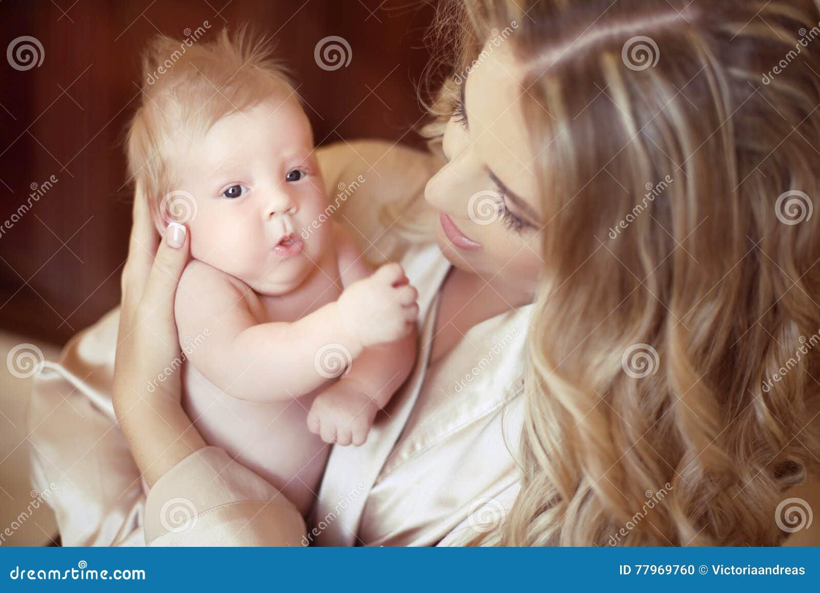 Junge Mutterholding ihr neugeborenes Schätzchen Mutter, die mit neugeborenem spielt