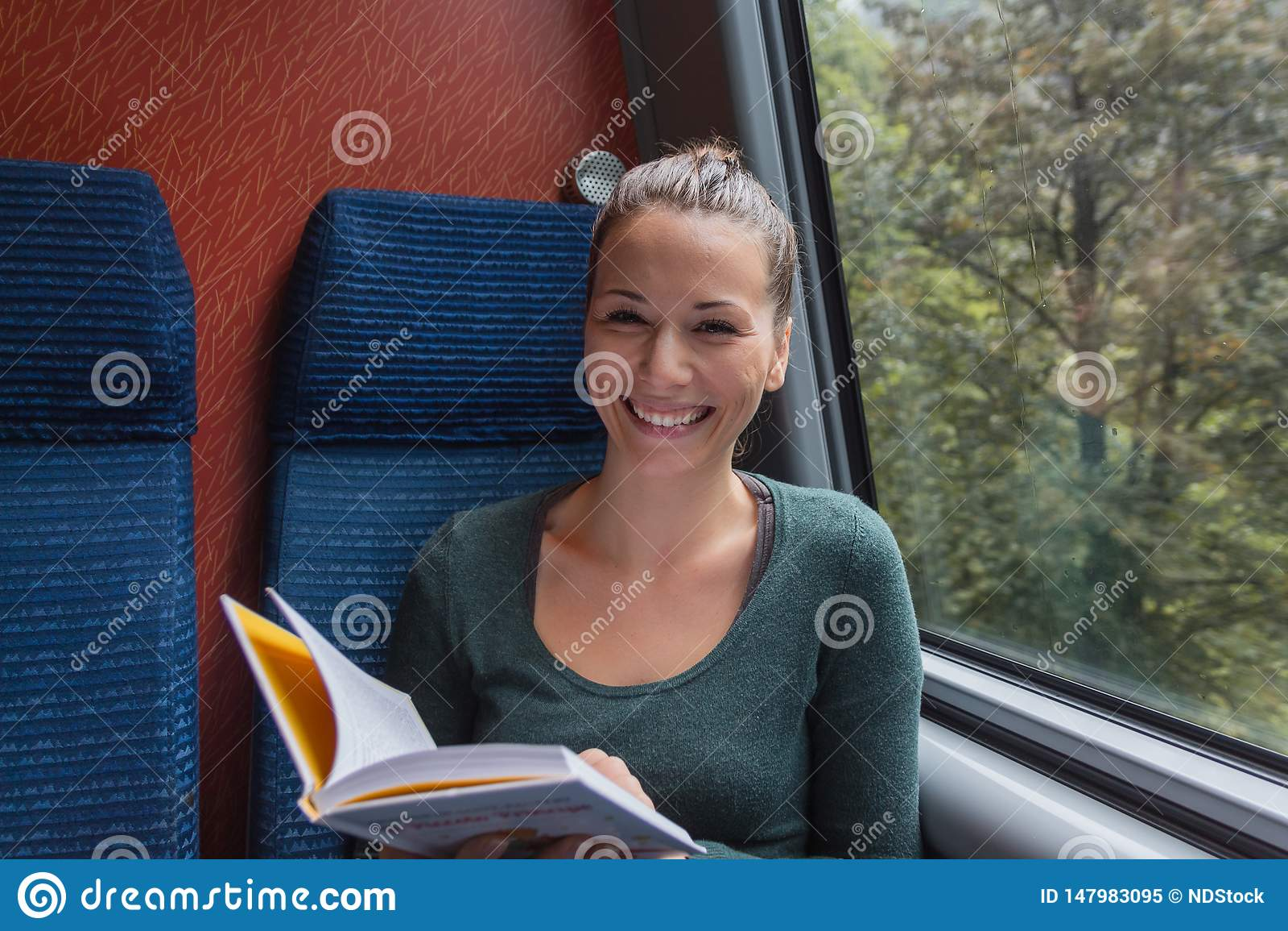 Junge nette Frau, die ein Buch beim Reisen mit dem Zug lächelt und liest