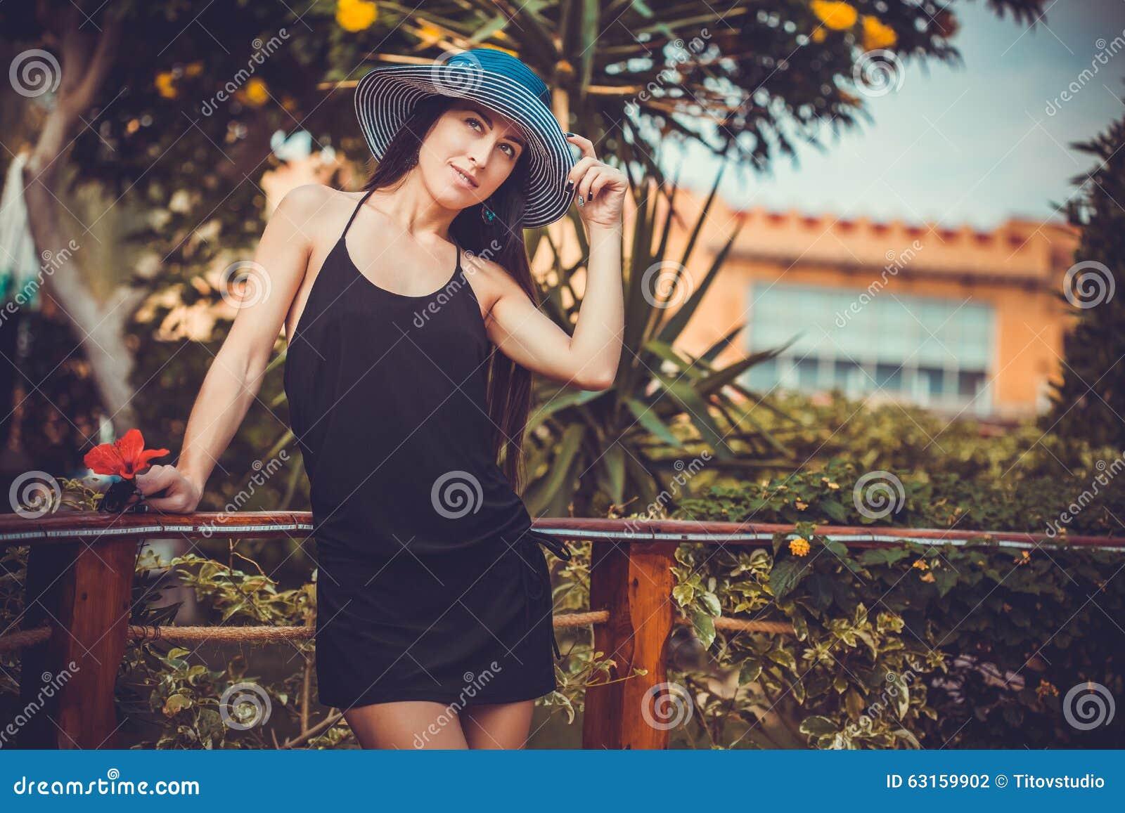 Junge nette Frau, die in einem grünen Park aufwirft