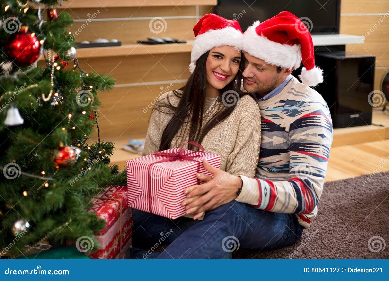 Junge Paare In Den Weihnachtshüten, Die Geschenke Halten Stockbild ...