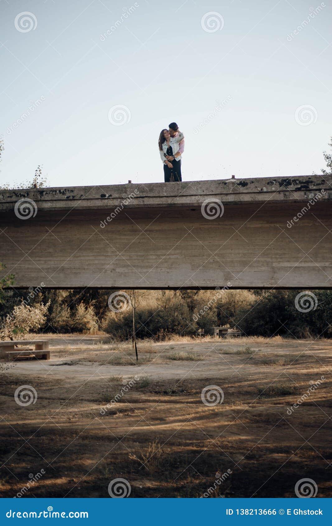 Junge Paare in der Liebe, die auf einer alten Brücke umarmt