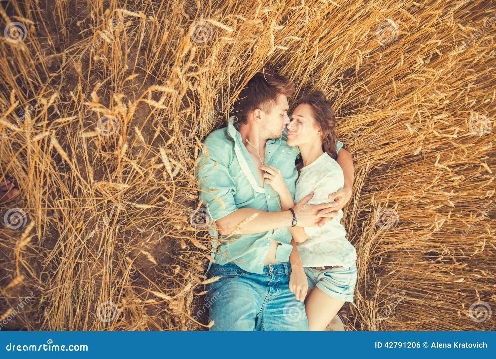 Junge Paare in der Liebe im Freien Verbinden Sie das Umarmen Junge schöne Paare in der Liebe, die auf dem Feld auf Sonnenuntergan