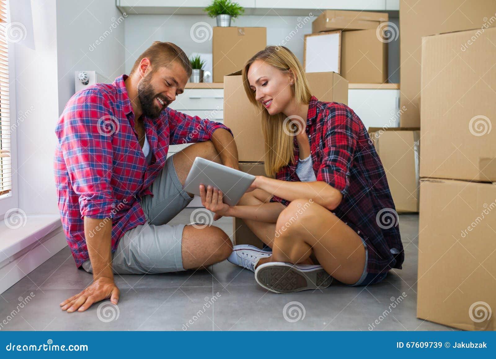 Junge Paare Die Auf Dem Boden Mit Tabletten Pc Sitzen Und Fu Wählen