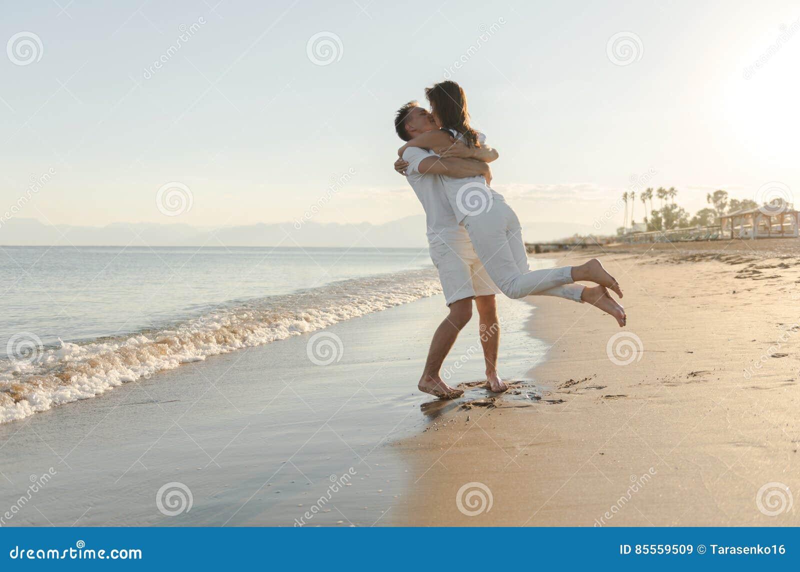 Junge Paare, die am Strand spielen