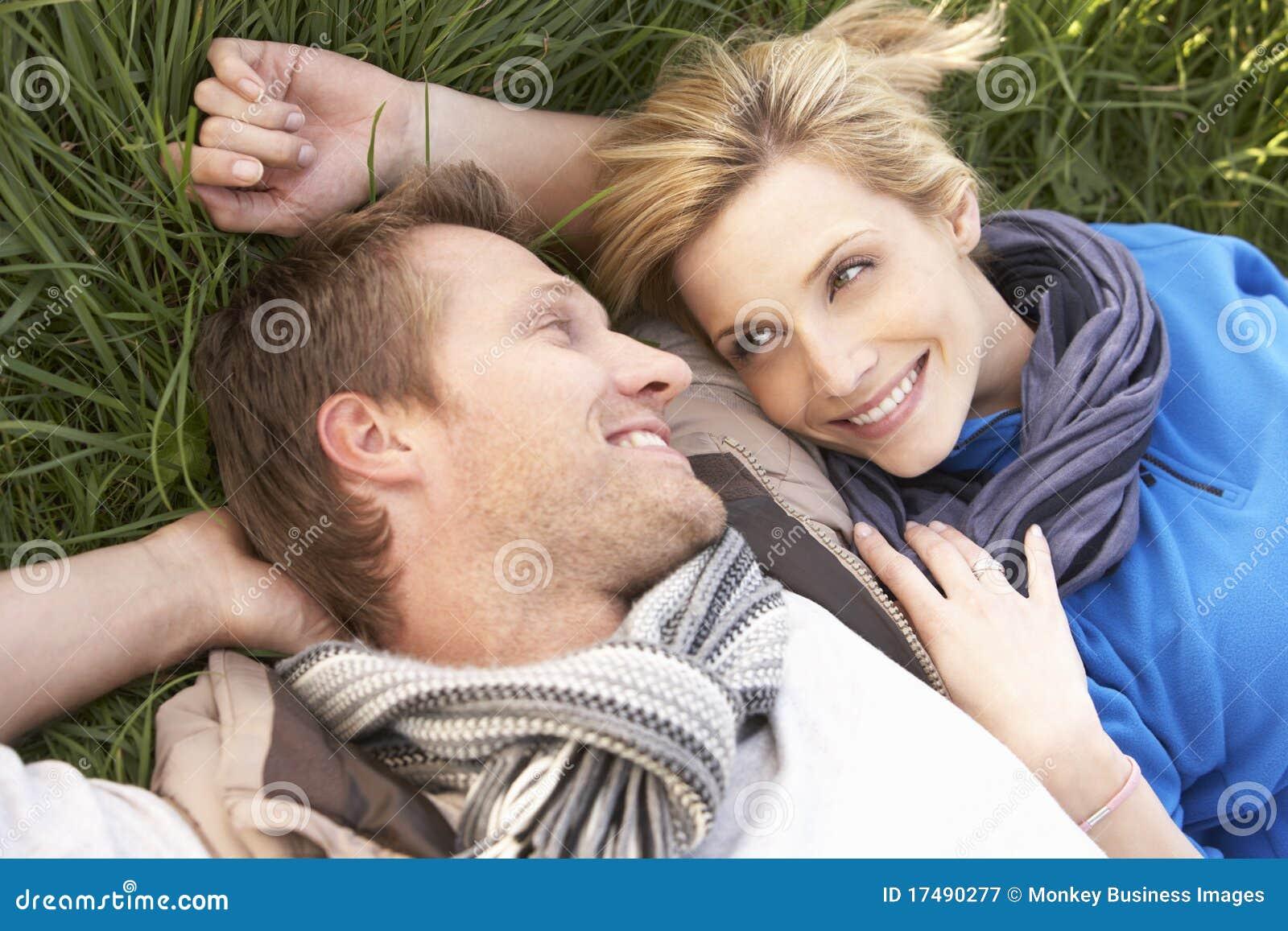 Junge Paare, die zusammen auf Gras liegen