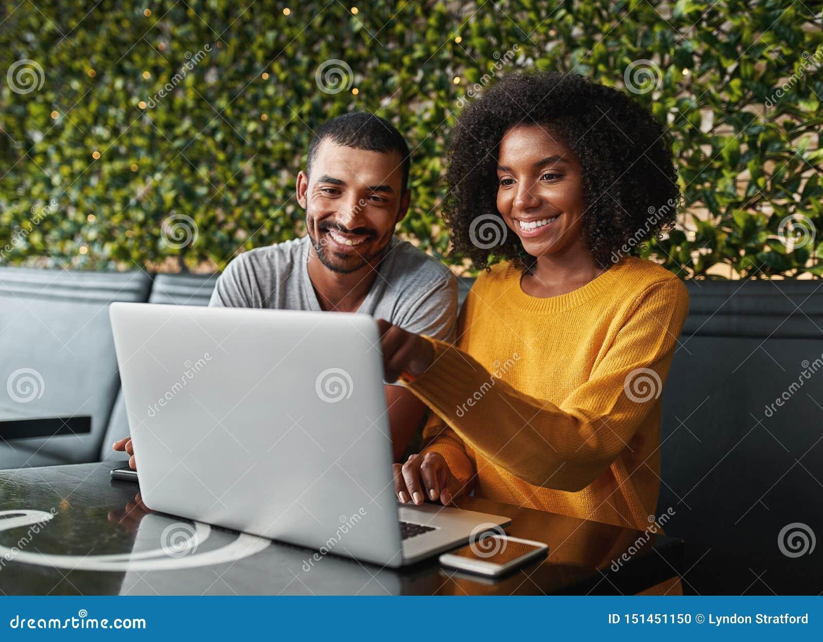 Junge Paare im café, das Laptop betrachtet