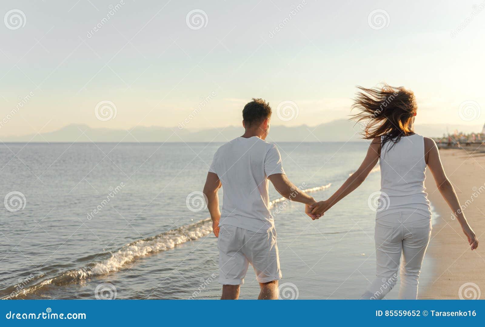 Junge Paare laufen gelassen weg auf dem Strand