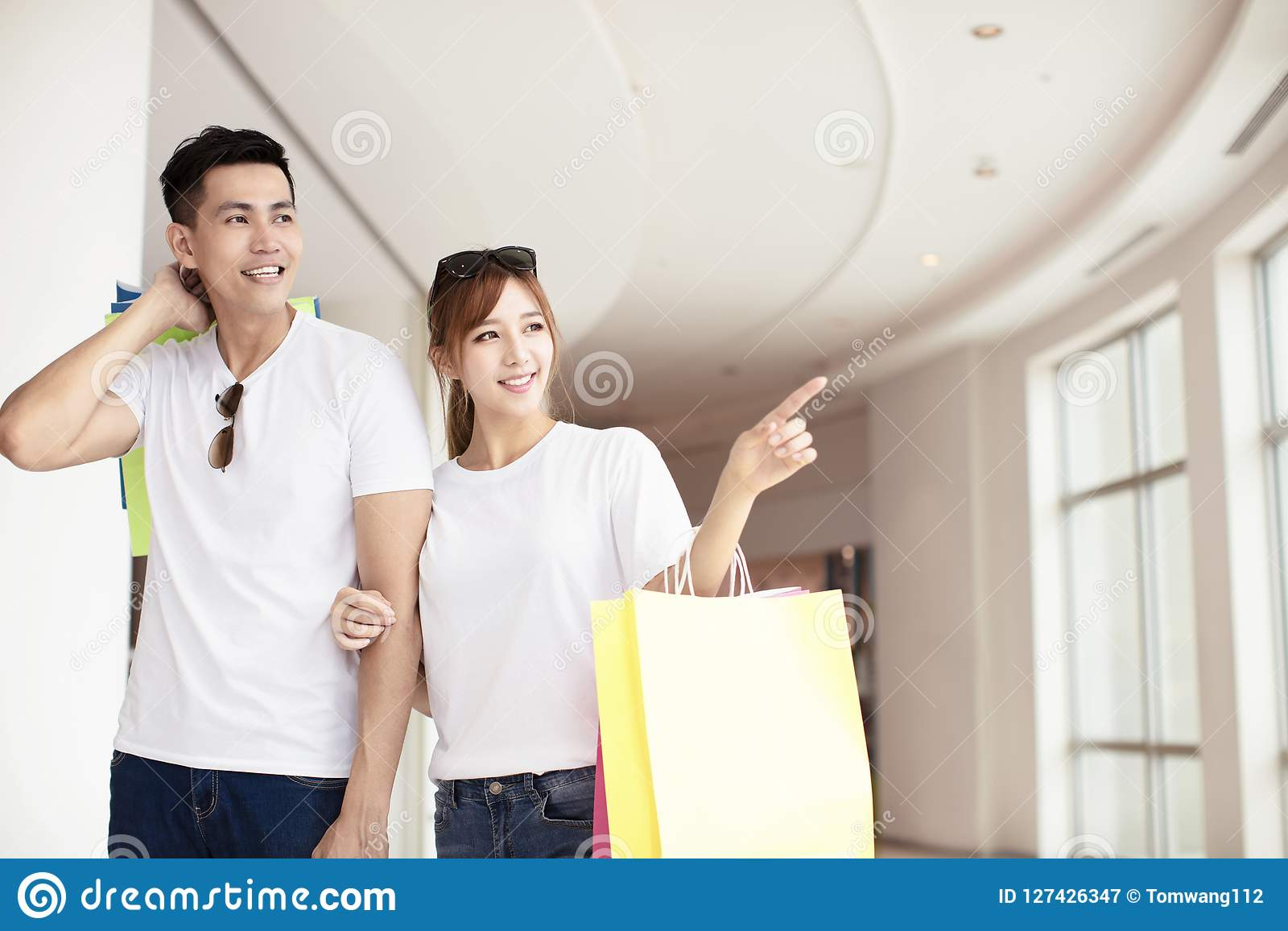 Junge Paare mit den Einkaufstaschen, die in Mall gehen
