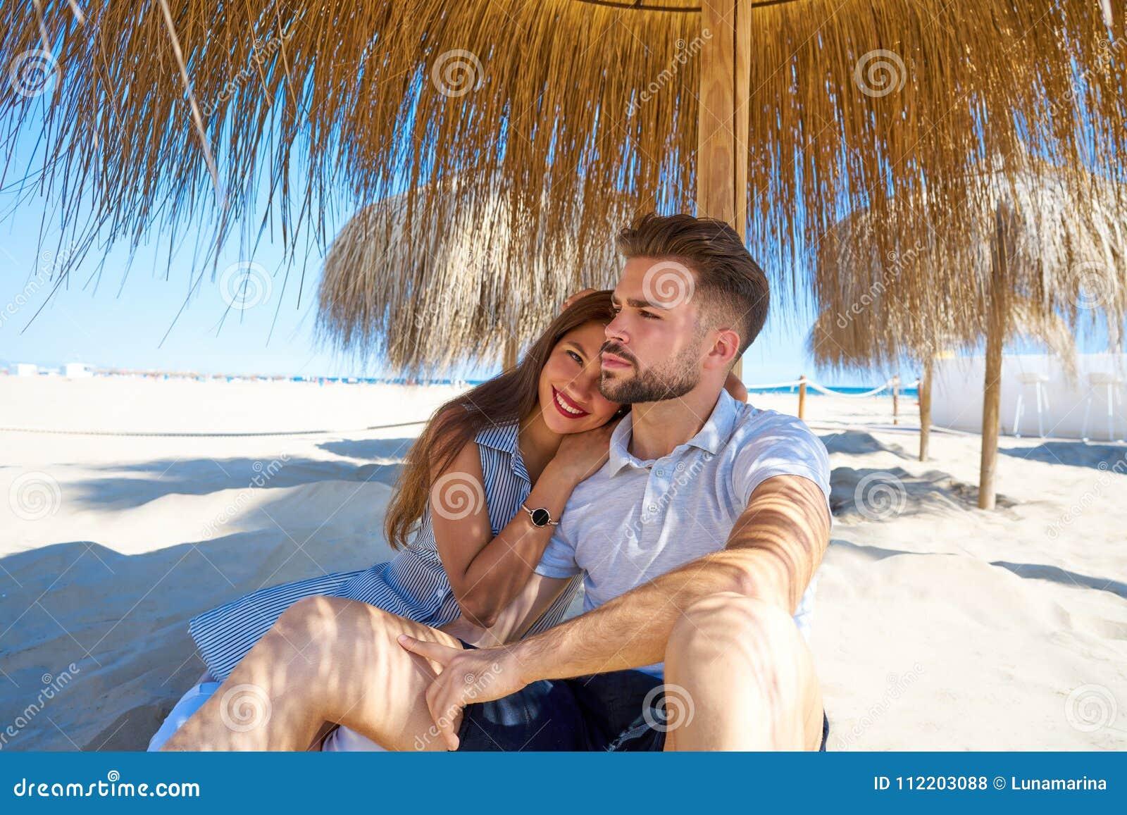 Junge Paare Umarmen In Einem Strand Unter Sonnenschirm Stockfoto ...