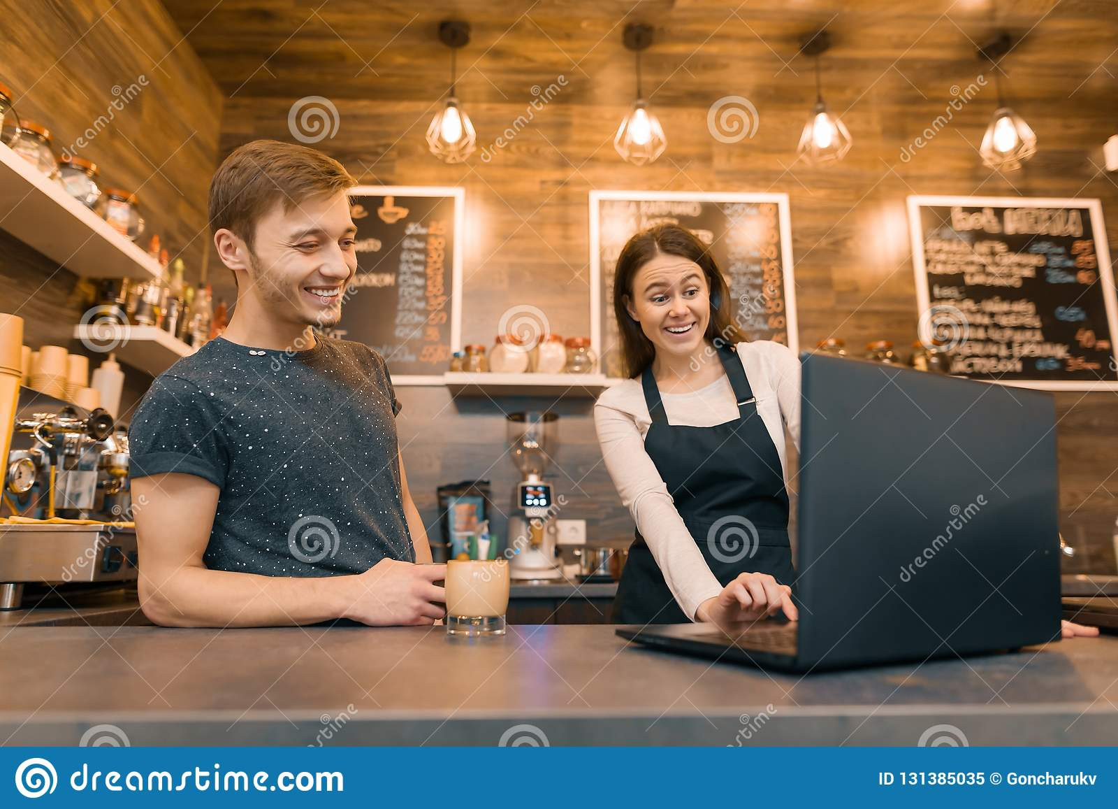 Junge Paarmann- und -fraueninhaber des kleinen modernen Kaffeehauses unter Verwendung der Laptop-Computers für Arbeit
