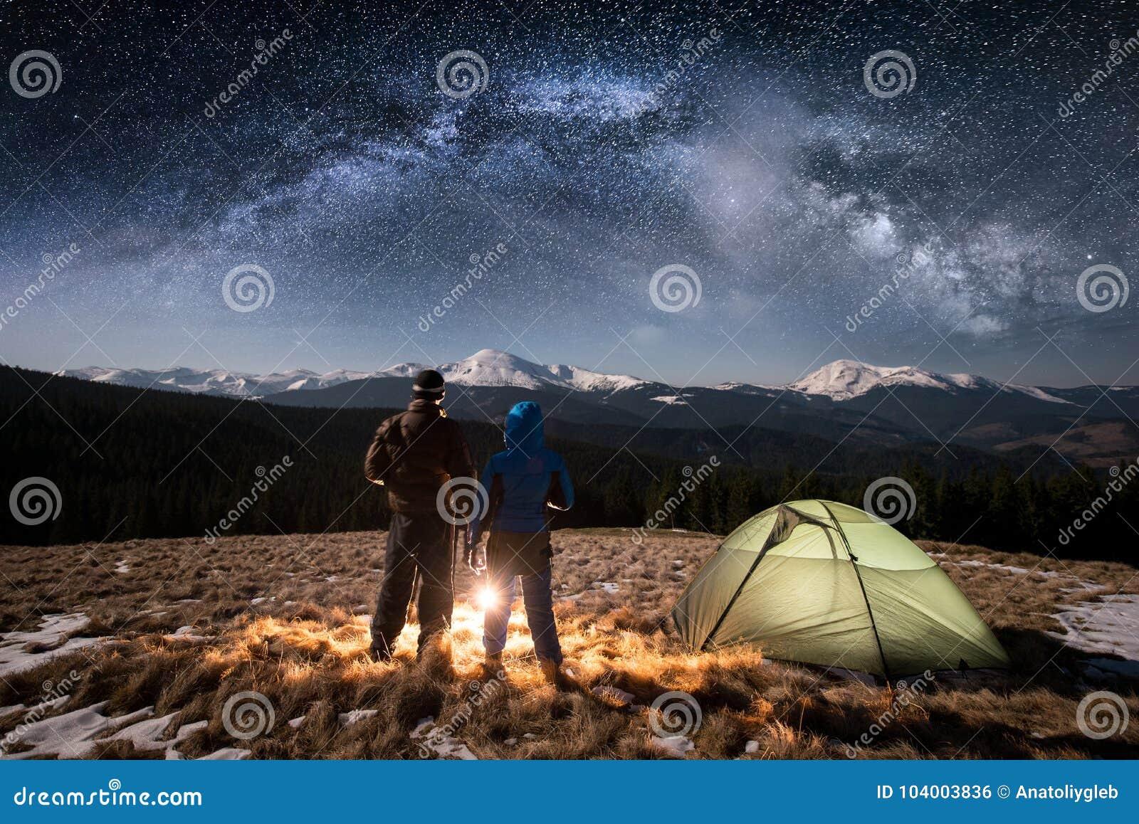 Junge Paartouristen der hinteren Ansicht, die einen Rest in nah darunter kampieren am nächtlichen Himmel voll von Sternen und von