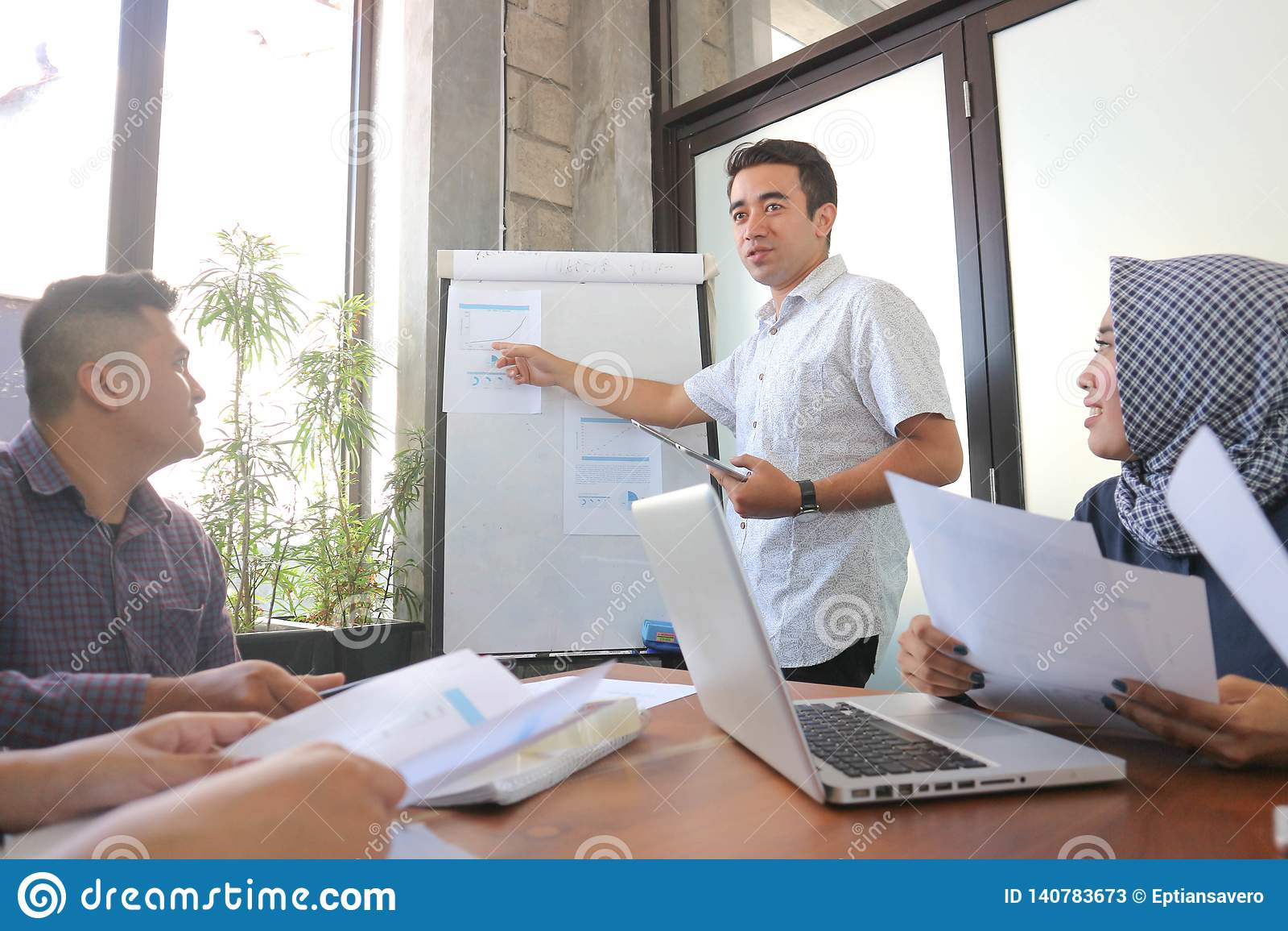 Junge professionelle männliche Darstellung bei der Gruppensitzung im weißen Brett mit Tablette und Laptop, Bürositzungsgruppe nah