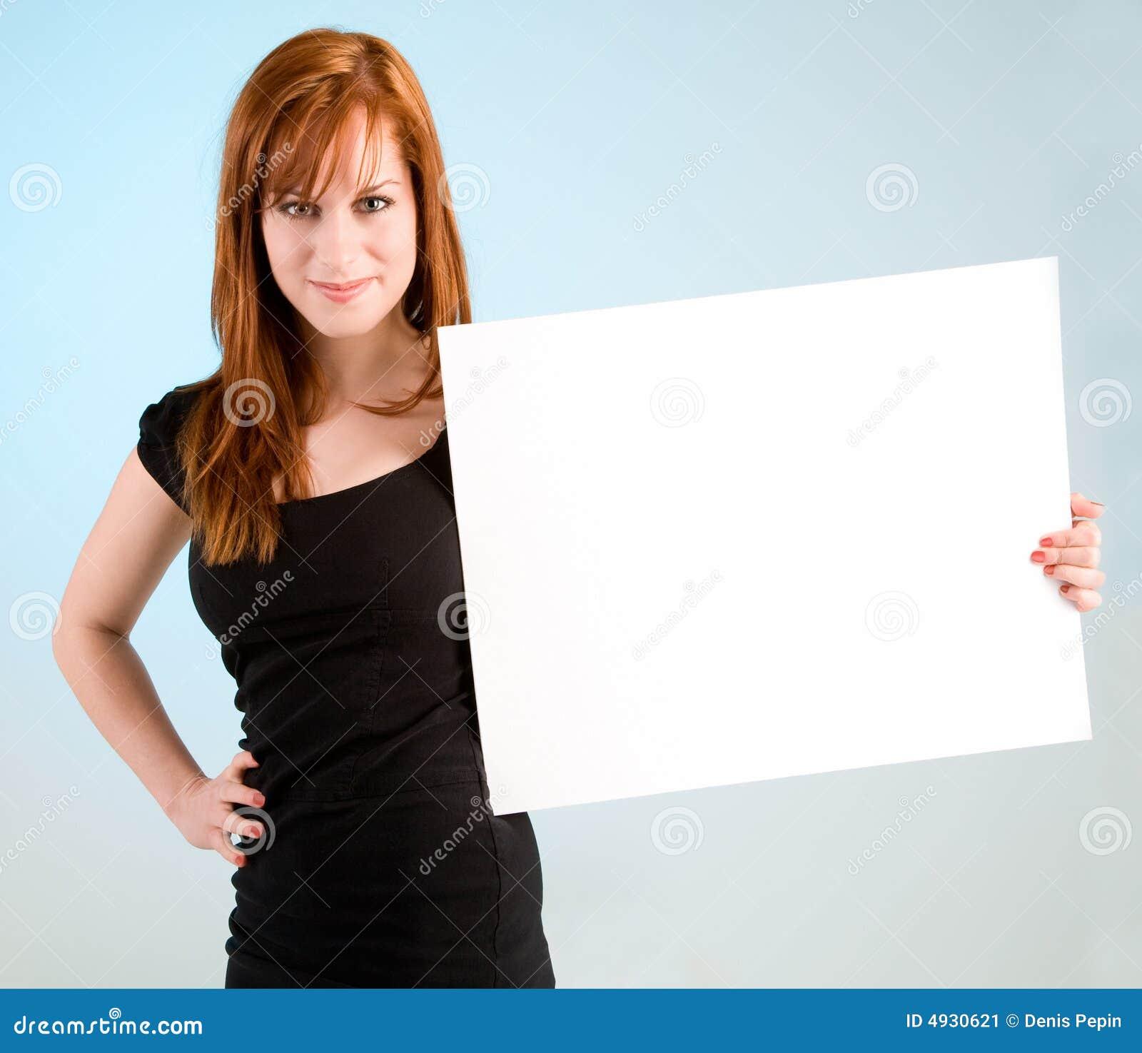 Junge Redhead-Frau, die ein unbelegtes weißes Zeichen anhält