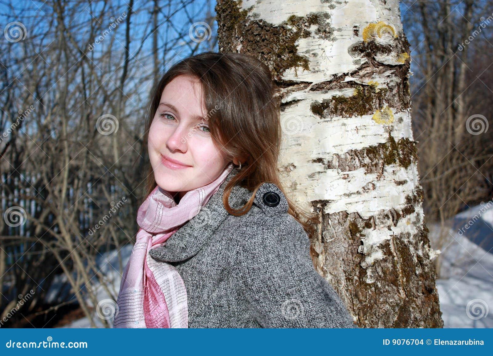 Junge russische Frau nahe bei einer Birke