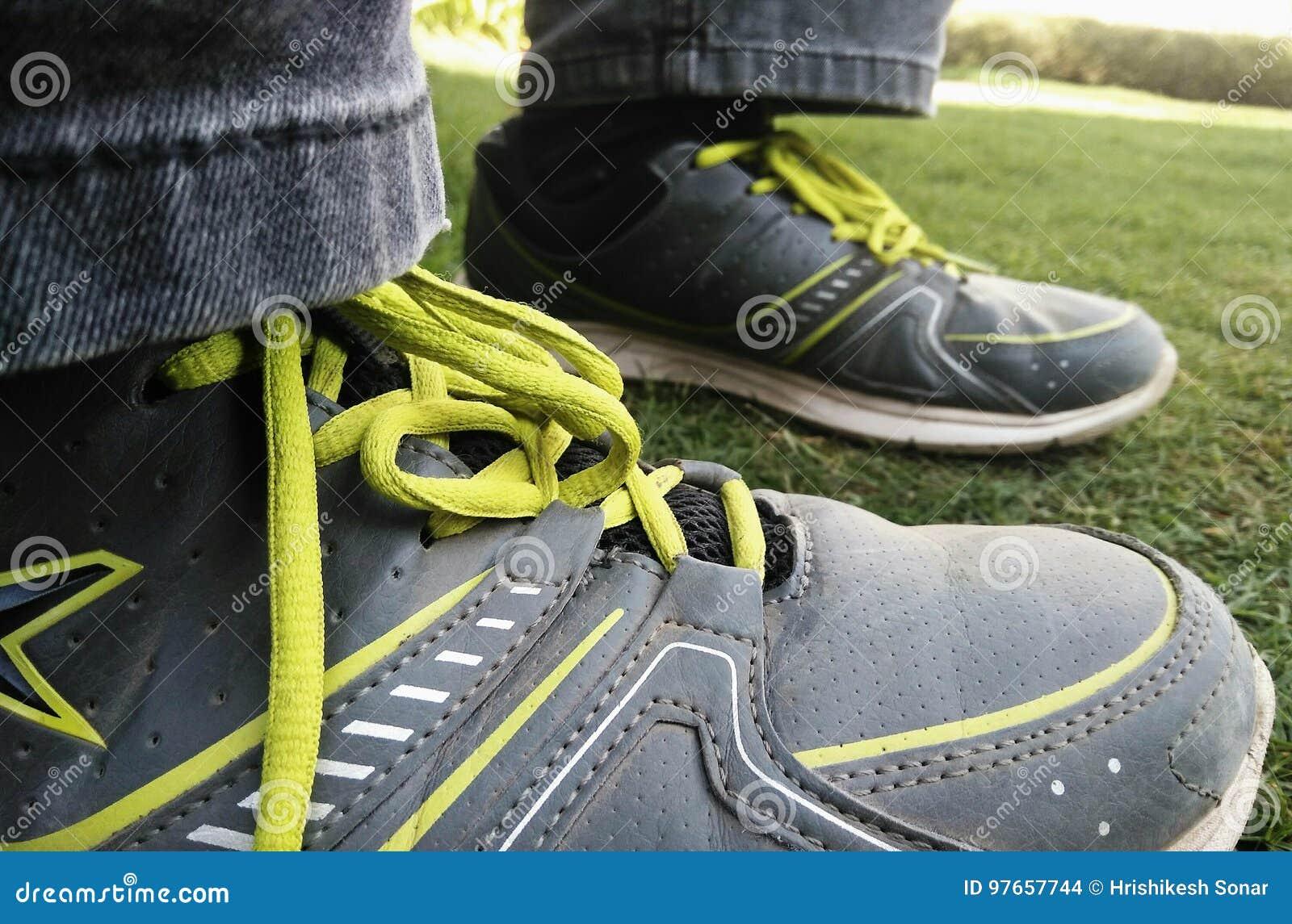 Junge ` s Beine auf dem Gras, das allein in Park-tragenden Sport-Schuhen sitzt
