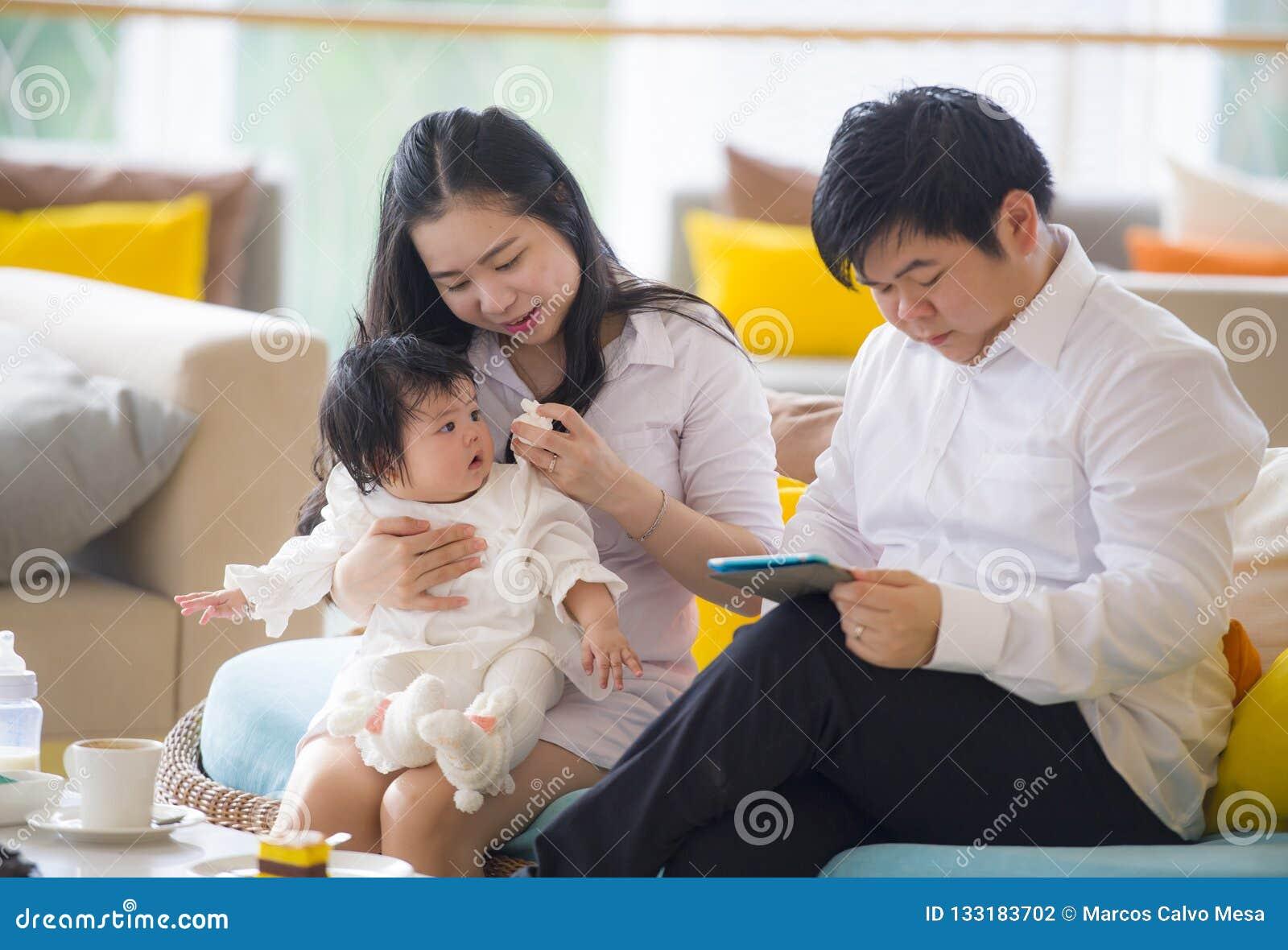 Junge schöne asiatische chinesische Familie, die am modernen Erholungsort mit dem Workaholicmannarbeitsgeschäft on-line mit digit