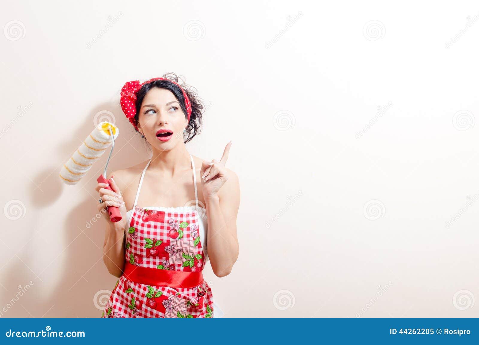 Junge schöne Brunettedame im Spaß, der Farbenkissen hält u. die Überholung von Idee zeigend mit dem Finger oben schaut hat