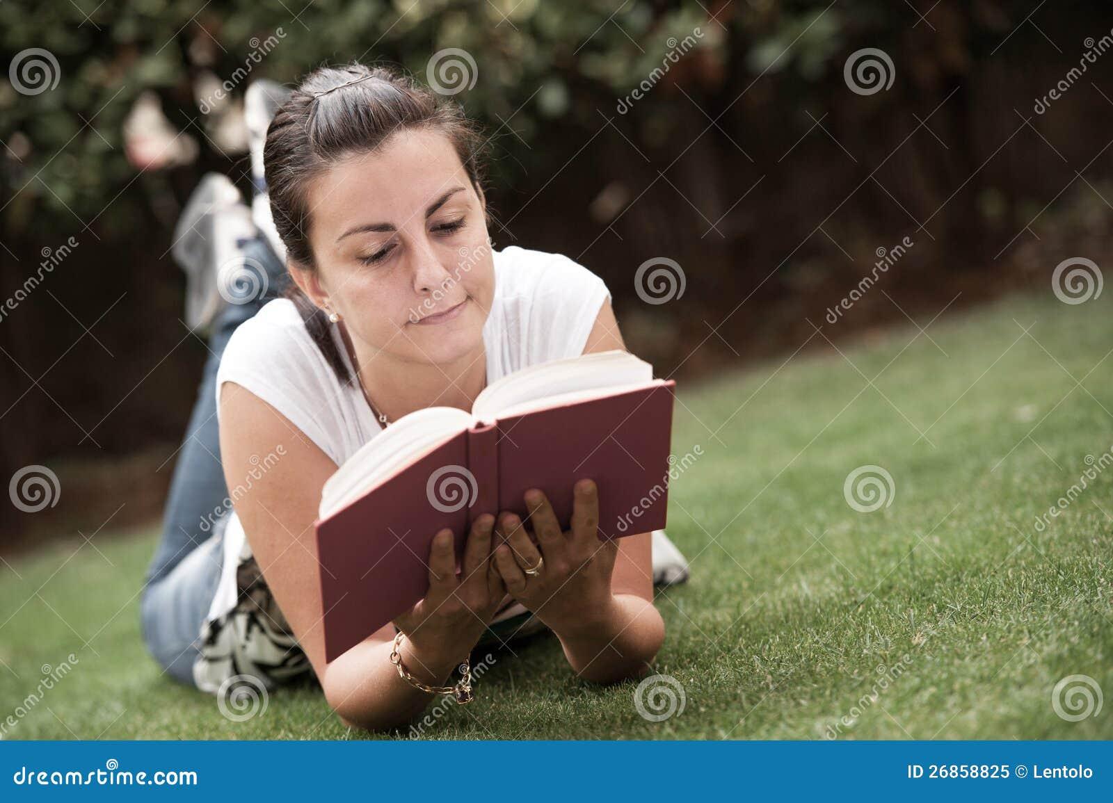 Junge schöne Frauenlagen auf grünem Feld